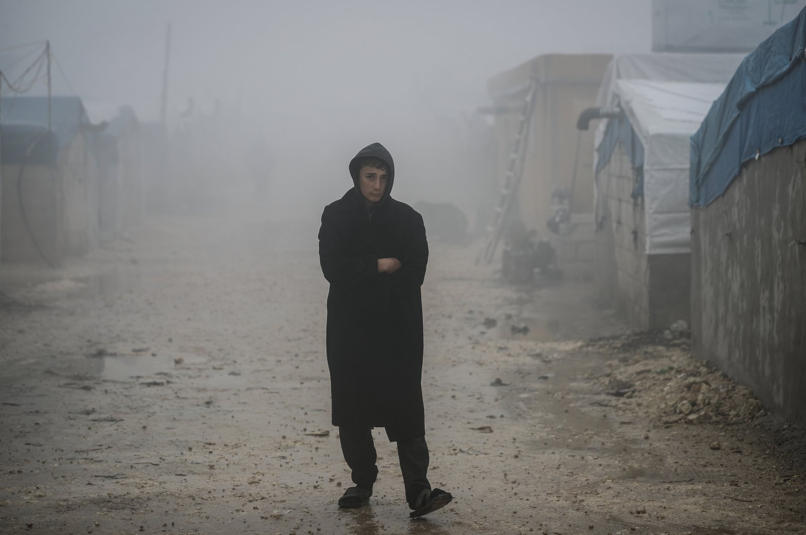 ASyrian boy stands on a muddy passage at a camp for internally displaced people, near the village of Barisha, Syria, Jan. 20, 2021. (Photo by Getty Images)