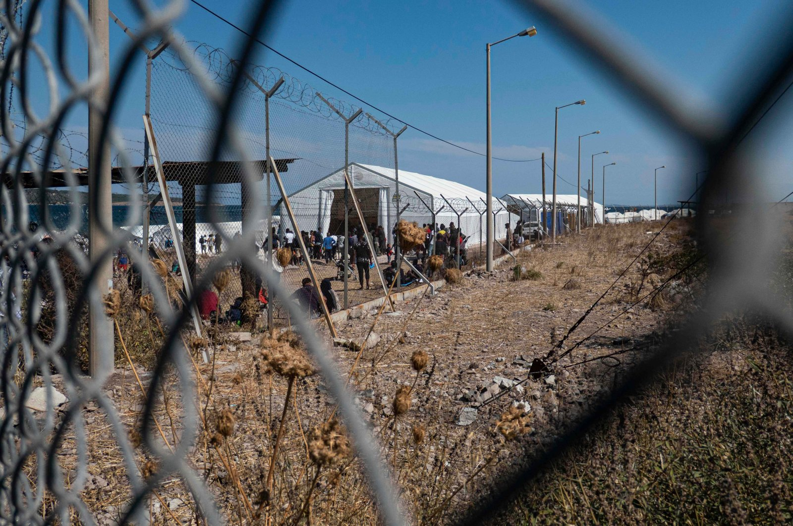 Asylum-seekers wait in front of large white tents bearing the UNHCR or UNICEF logo for supplies such asfood, beds and clothes at thenew temporary refugee camp in Kara Tepe, Lesbos, Greece, Sept. 20, 2021(Getty Images)