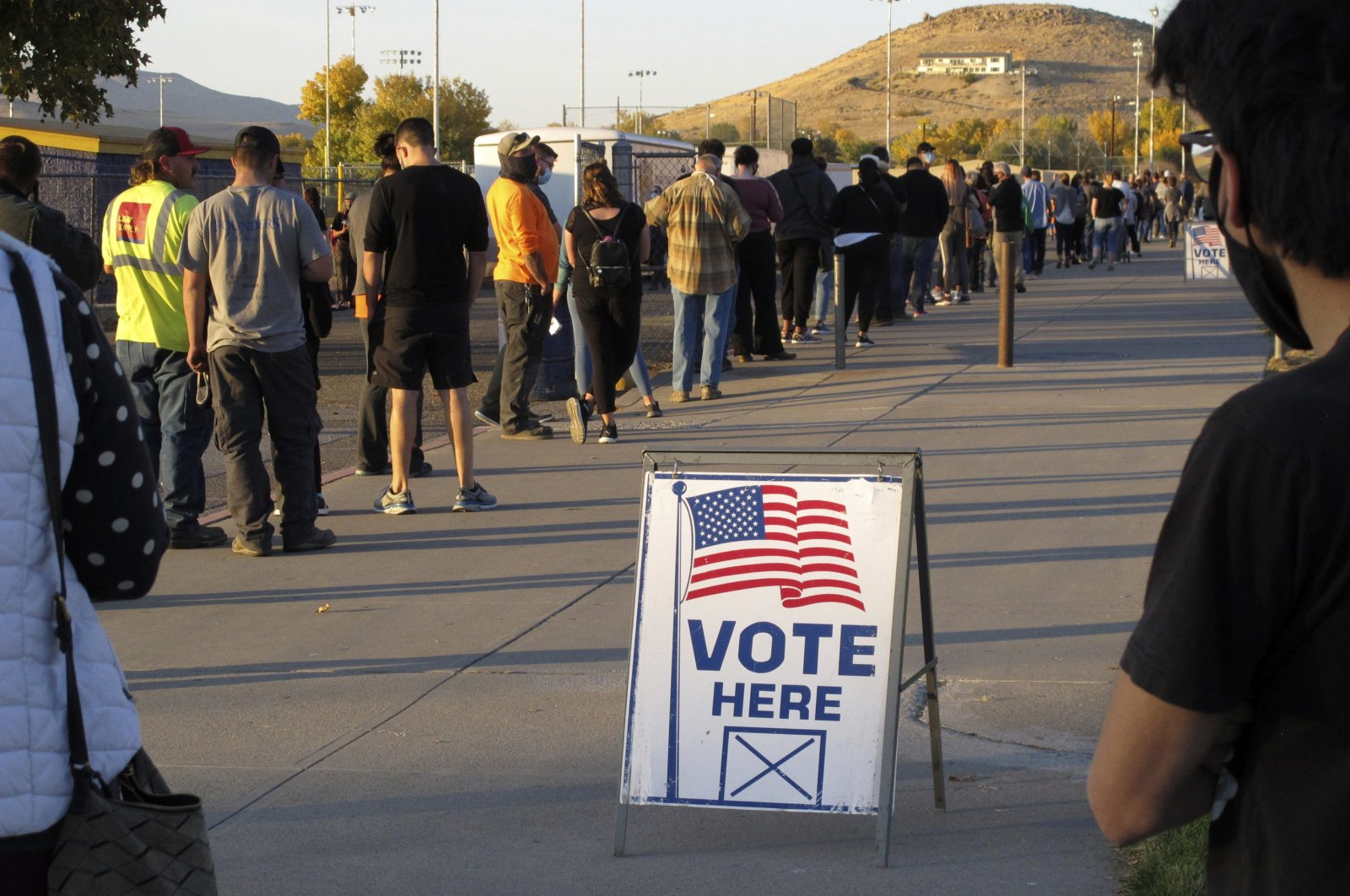 In this Nov. 3, 2020, file photo, mostly masked northern Nevadans wait to vote in-person at Reed High School in Sparks, Nev., prior to polls closing. (AP Photo)