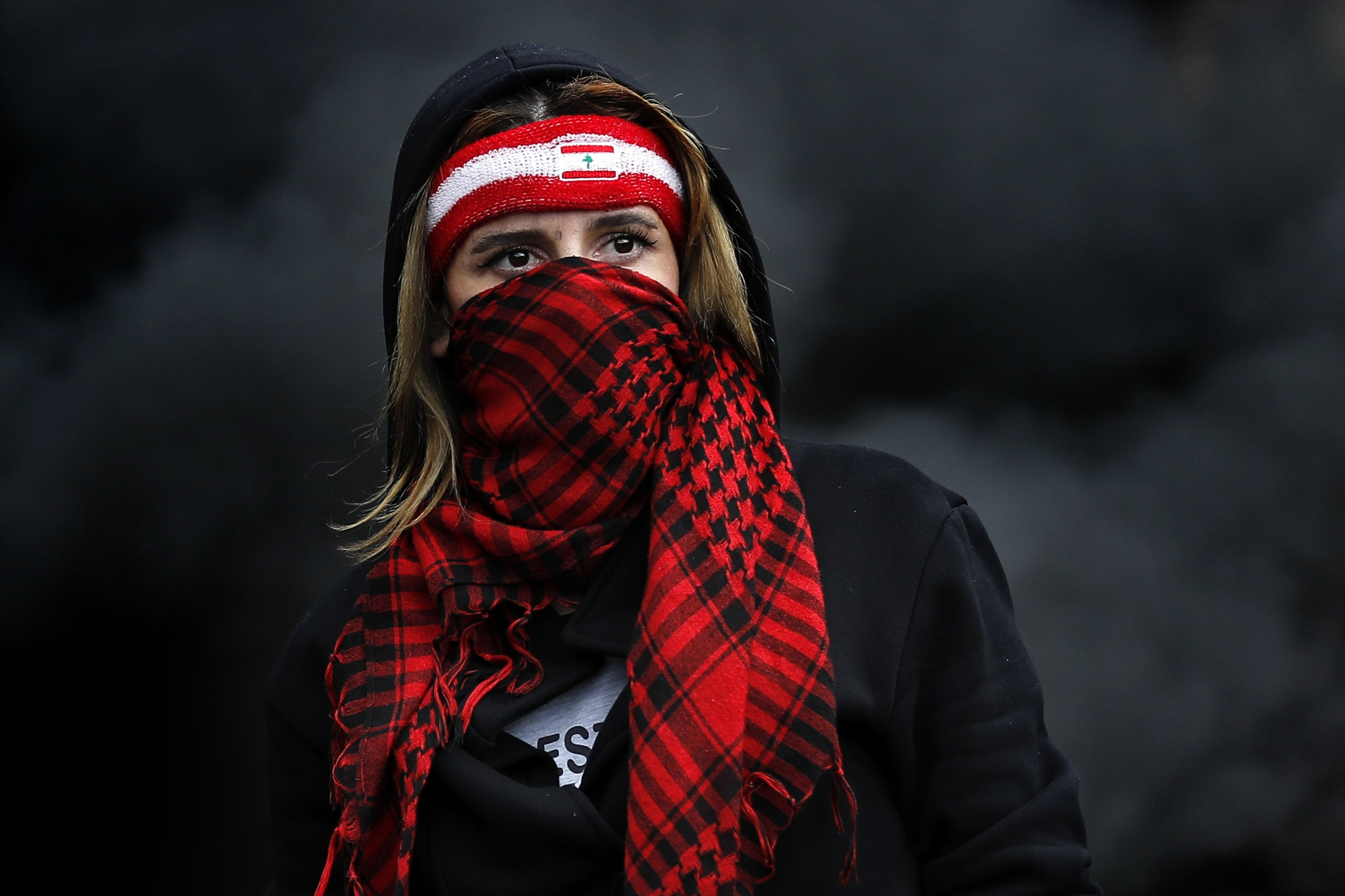 A protester covers her face with a scarf as she blocks a main highway during a protest in the town of Zouk Mosbeh, north of Beirut, Lebanon, March 8, 2021. (AP Photo)