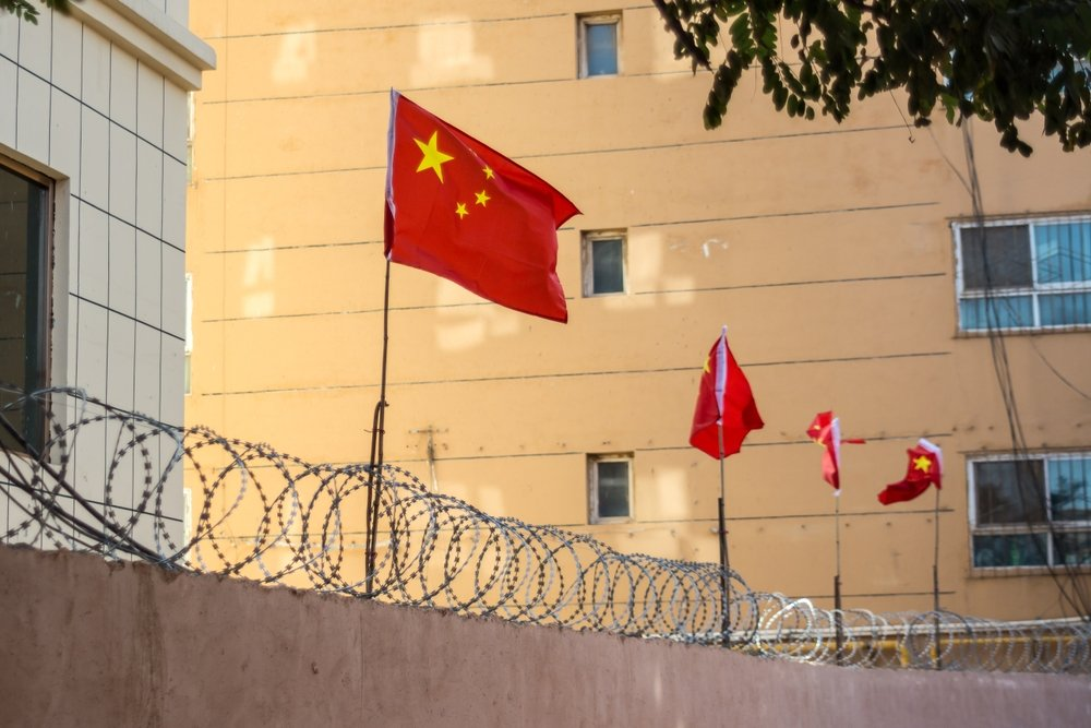 Chinese flags line a barbed wired wall in Kashgar, Xinjiang, China. (Shutterstock Photo)