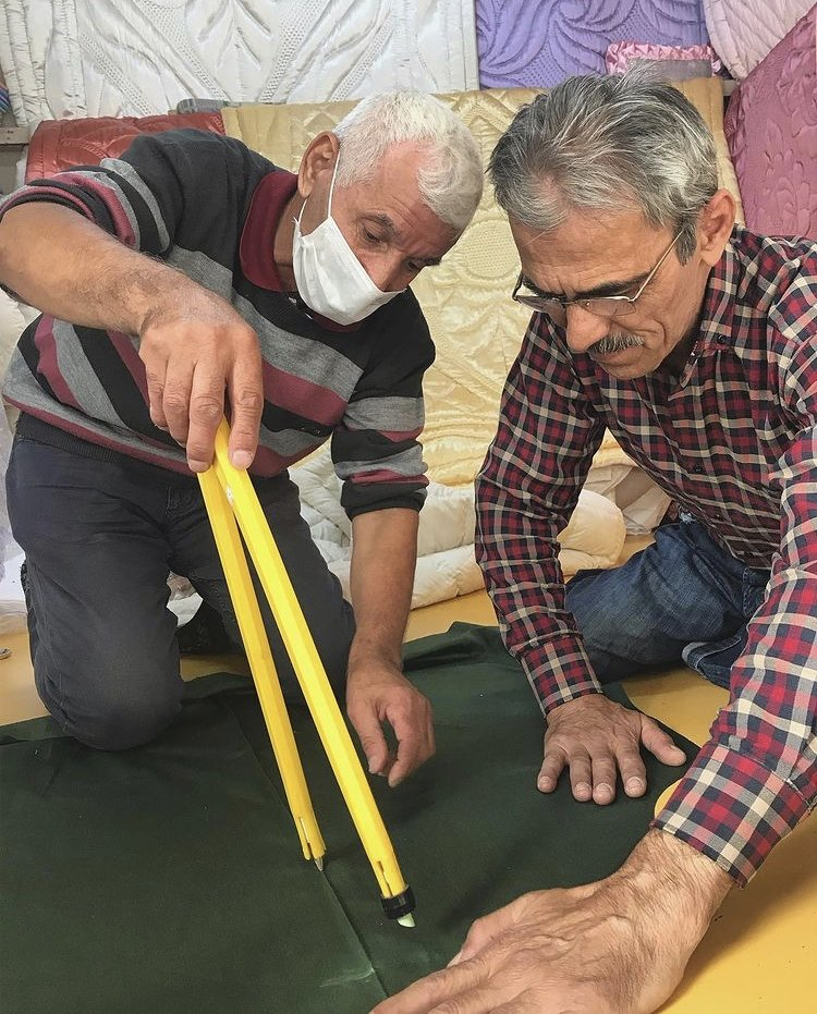 Rabia Gül's artisanal masters Ömer and Hikmet working on measuring fabric. (Photo courtesy of Rabia Gül)