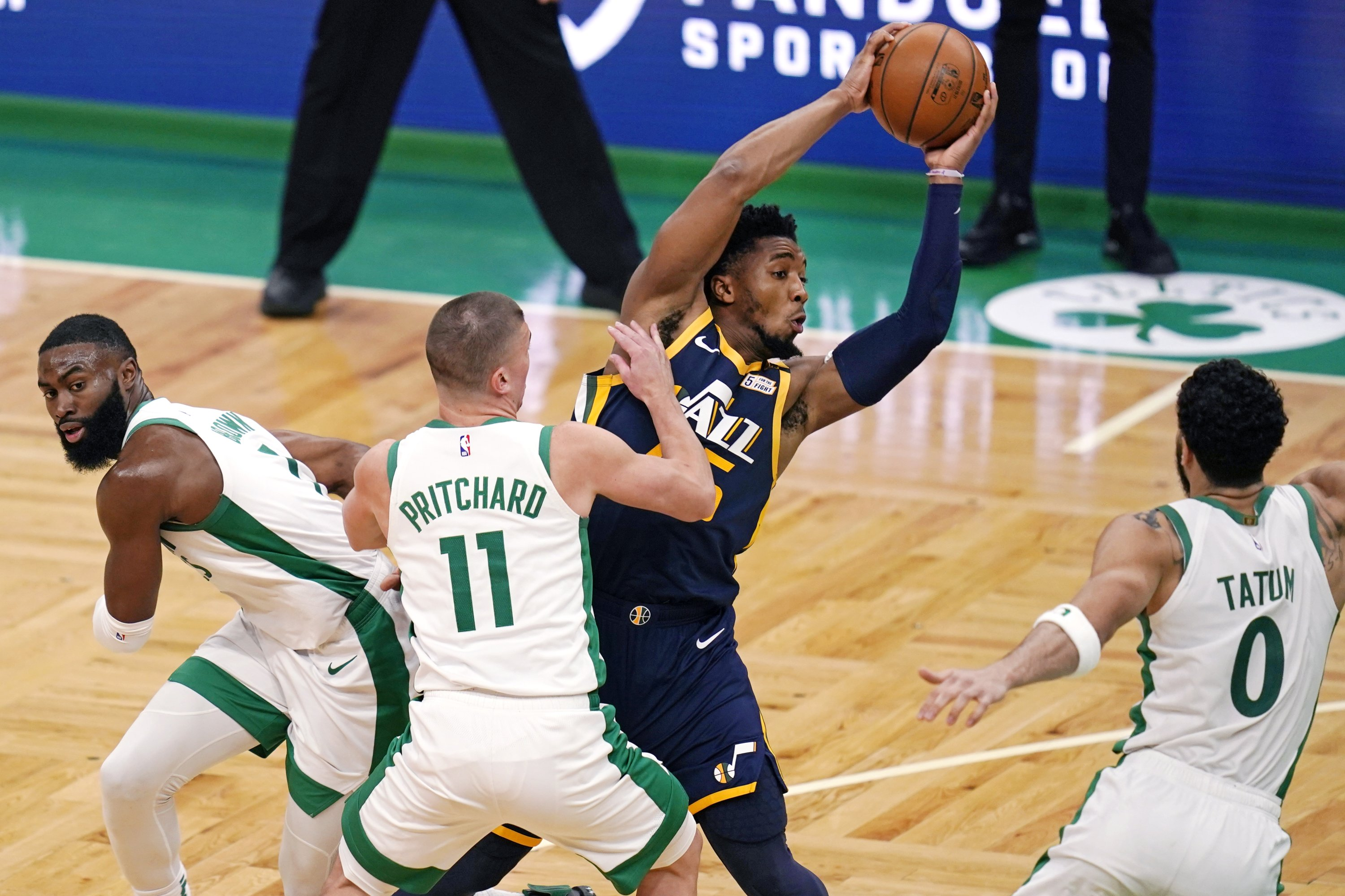 Utah Jazz guard Donovan Mitchell (C) looks to pass the ball while guarded by Boston Celtics' Jaylen Brown (L), guard Payton Pritchard (2nd L) and forward Jayson Tatum (R) during an NBA game, Boston, U.S., March 16, 2021. (AP Photo)