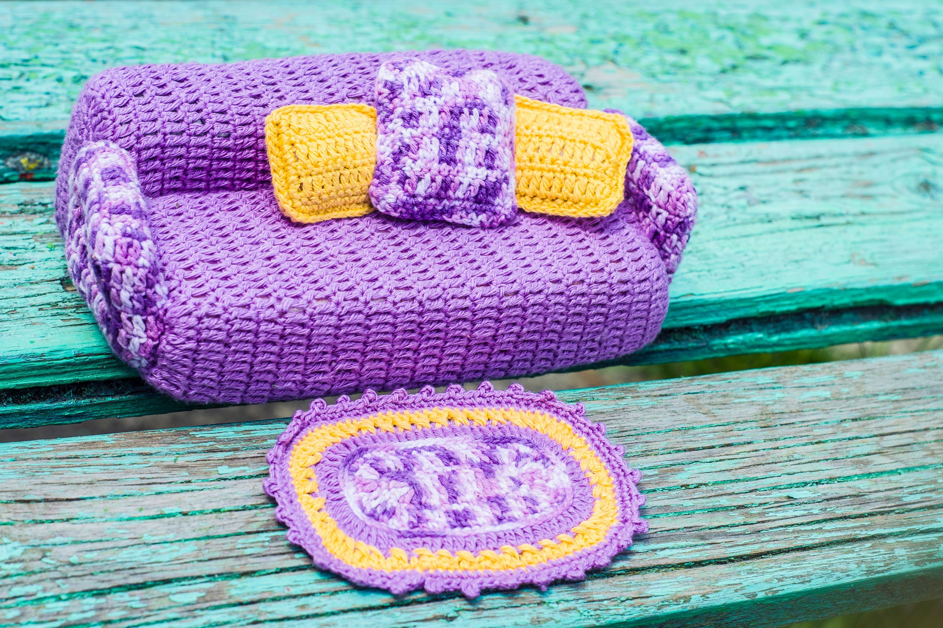 A small crocheted couch with some tiny cushions and a small rug to complete the cozy corner for cats and dolls alike. (Shutterstock Photo)