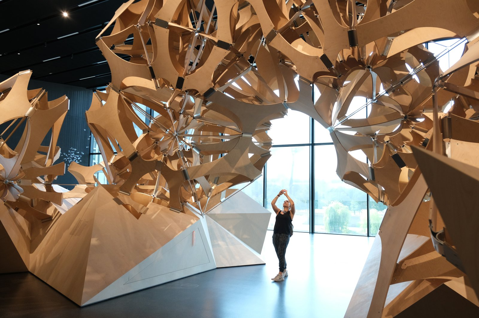A visitor photographs a wooden sculpture made of over 6,000 parts and meant to depict the complexity of nature during a press preview at the new Futurium museum in the city center in Berlin, Germany, Aug. 27, 2019. (Getty Images)