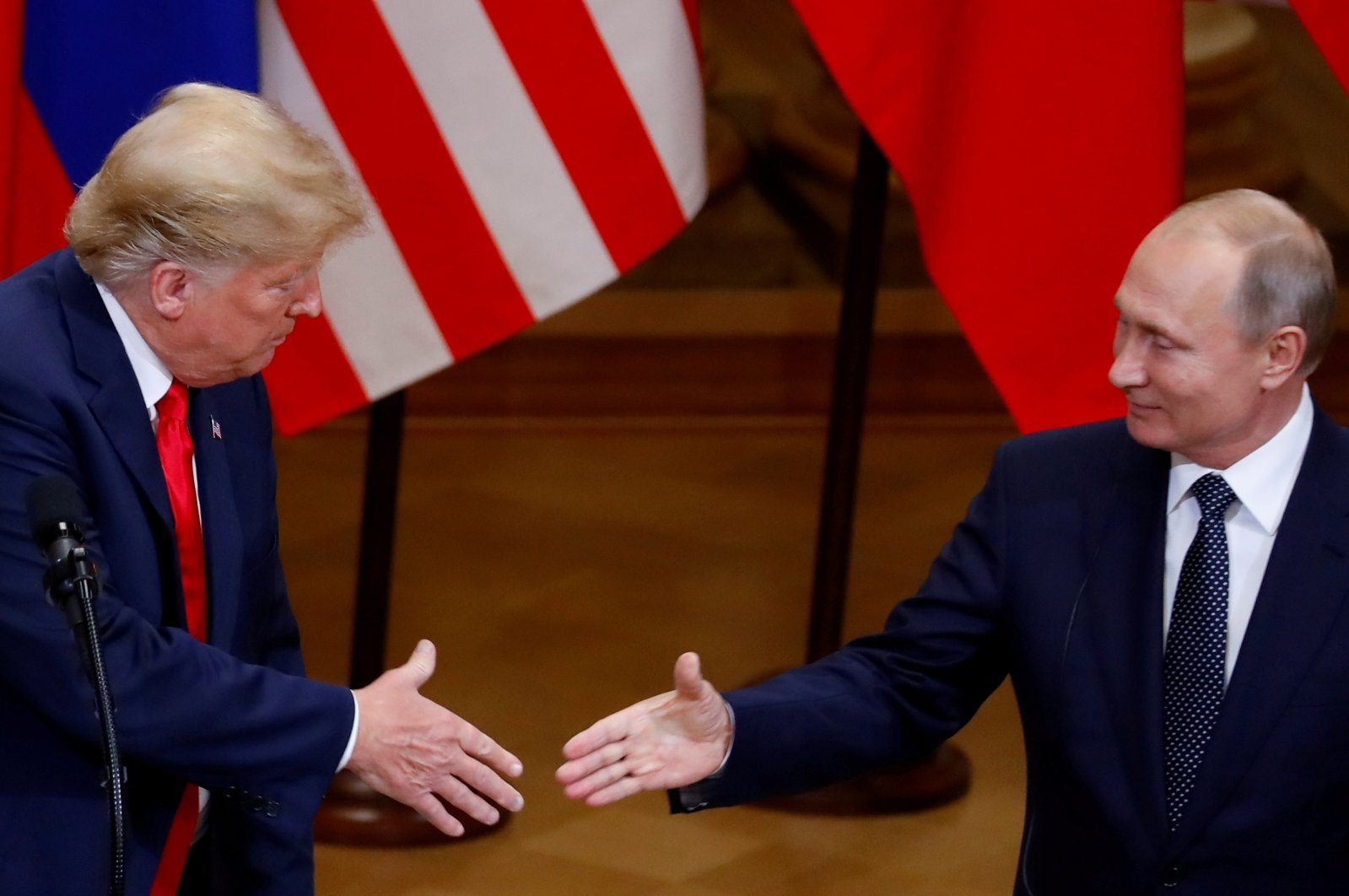Former U.S. President Donald Trump and Russian President Vladimir Putin shake hands as they hold a joint news conference after their meeting in Helsinki, Finland, July 16, 2018. (Reuters Photo)