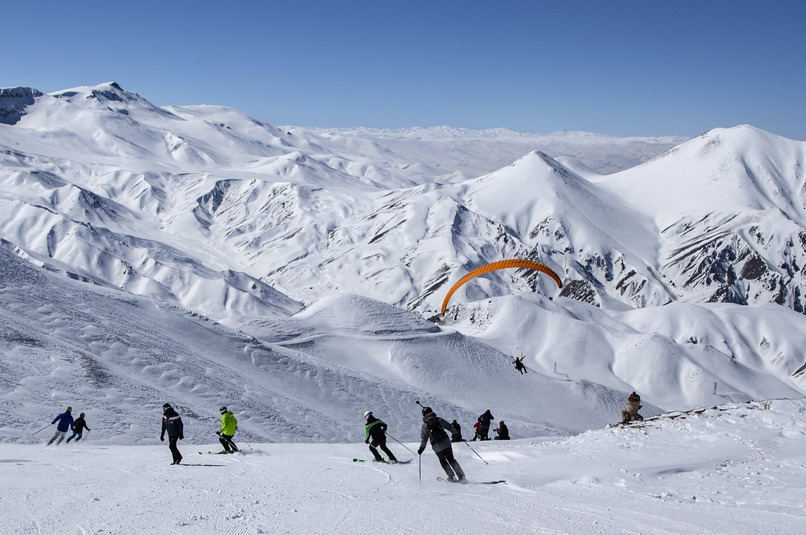 People ski on a slope of Palandöken mountain, one of the prominent winter tourism spots in the country, as a paraglider takes off during the COVID-19 in Erzurum, Turkey, March 4, 2021. (EPA Photo)