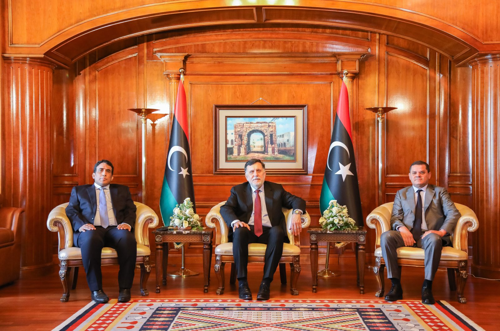 Libya's Prime Minister Abdul Hamid Dbeibeh (R), Libya's internationally recognized former Prime Minister Fayez Sarraj (C), and Mohammed al-Menfi (L), Head of the Presidency Council, pose for a photo ahead of the handover ceremony in Tripoli, Libya March 16, 2021. (AA)
