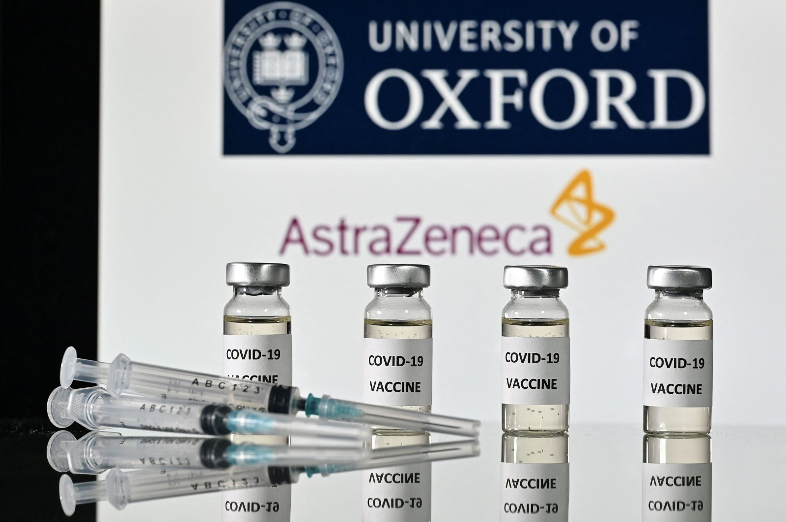 An illustration of vials and syringes in front of the logo of the University of Oxford and its partner British pharmaceutical company AstraZeneca, on Nov. 17, 2020. (AFP Photo)