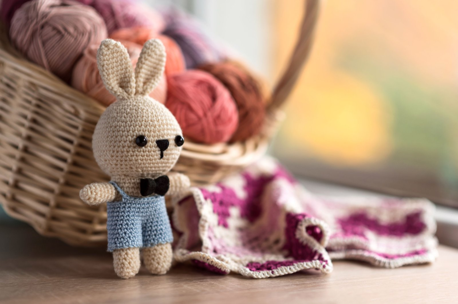 A little bunny amigurumi next to a granny square. (Shutterstock Photo)