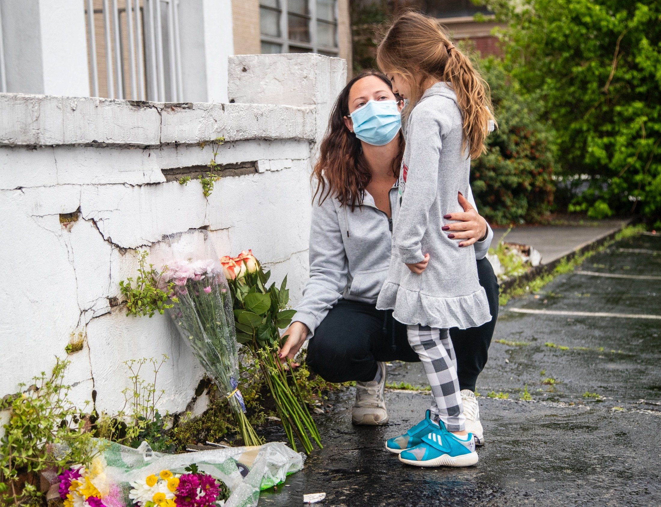 Mallory Rahman and her daughter Zara place flowers near a makeshift memorial outside of the Gold Spa in Atlanta, Georgia, U.S., March 17, 2021. (AP Photo)