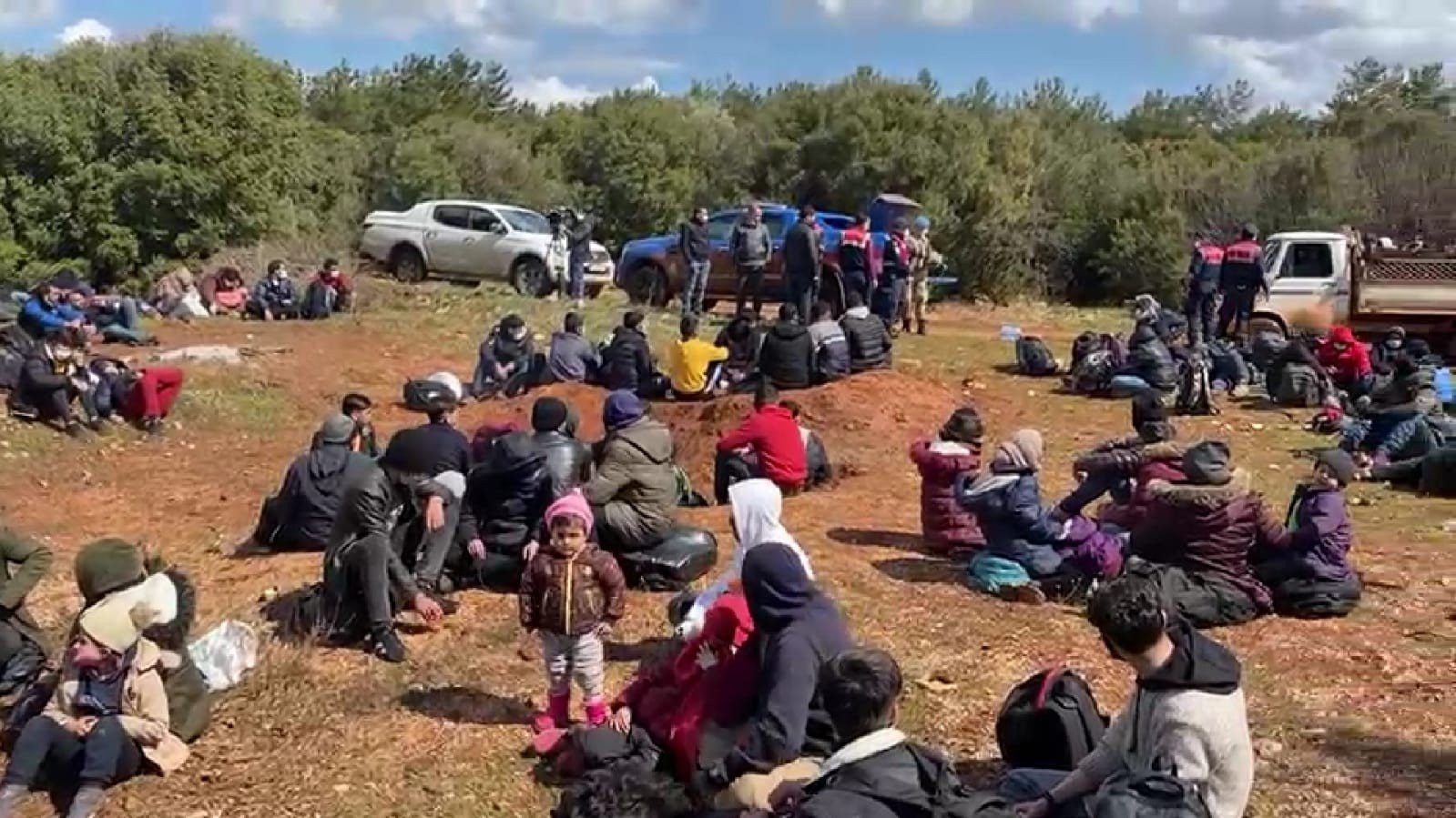 Irregular migrants wait to be processed after being rescued by Turkish Coast Guard in western Izmir province's Urla district on March 18, 2021 (IHA Photo)