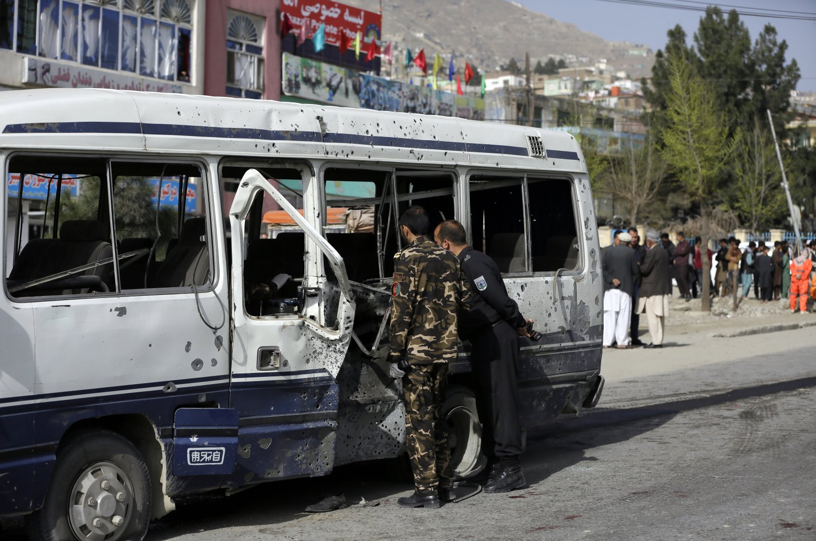 Security personnel inspects a damaged minibus after a bomb explosion in Kabul, Afghanistan, March 18, 2021. (AP Photo)