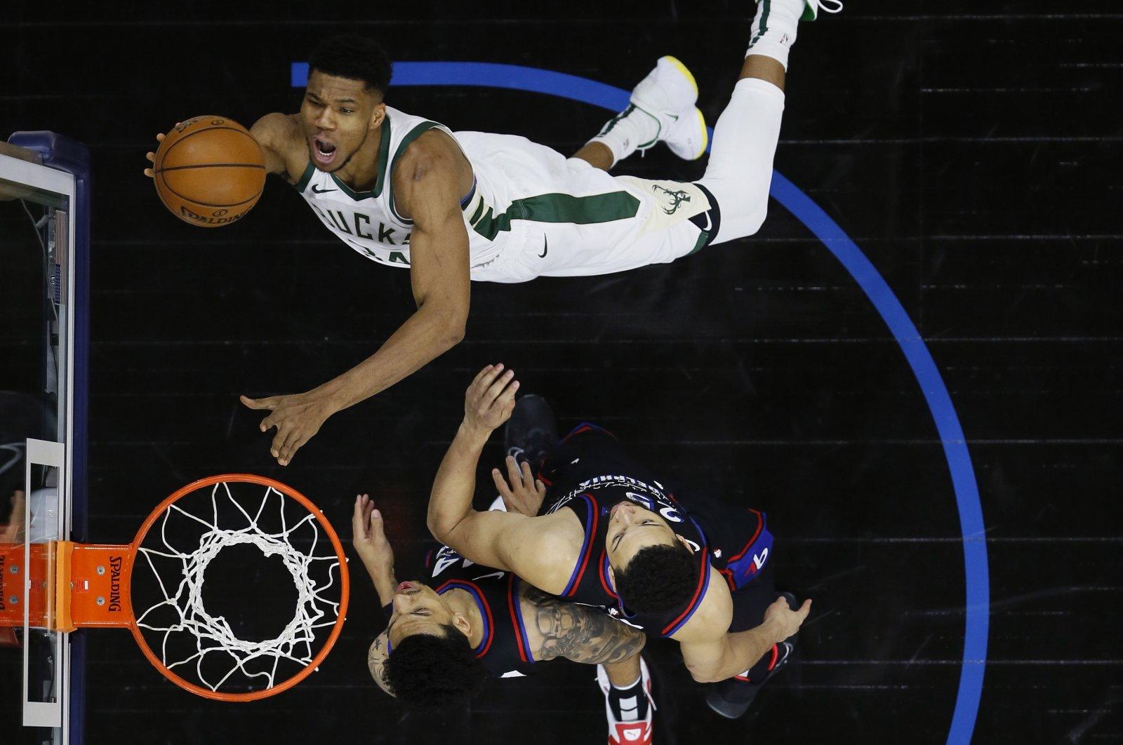 Milwaukee Bucks' Giannis Antetokounmpo, top, goes up for a shot against Philadelphia 76ers' Ben Simmons (C) and Danny Green during an NBA game, Philadelphia, Pennsylvania, March 17, 2021. (AP Photo)