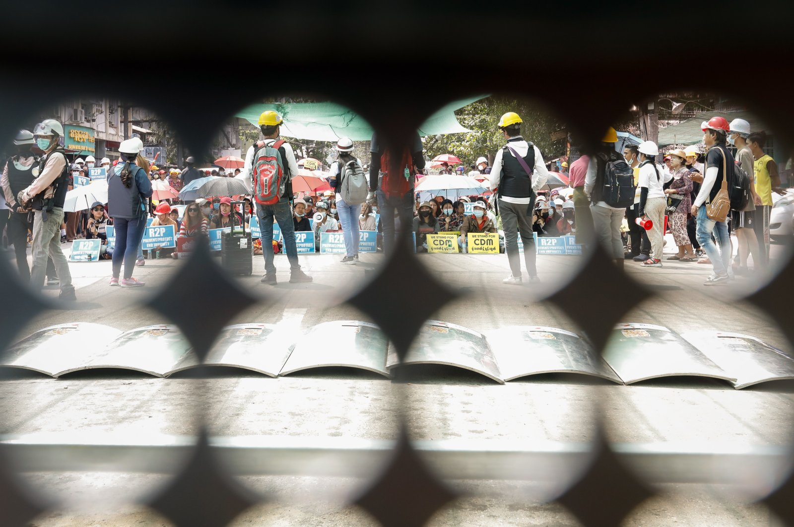 Demonstrators are seen from the holes of a shield during a protest against the military coup in Yangon, Myanmar, March, 18, 2021. (EPA)