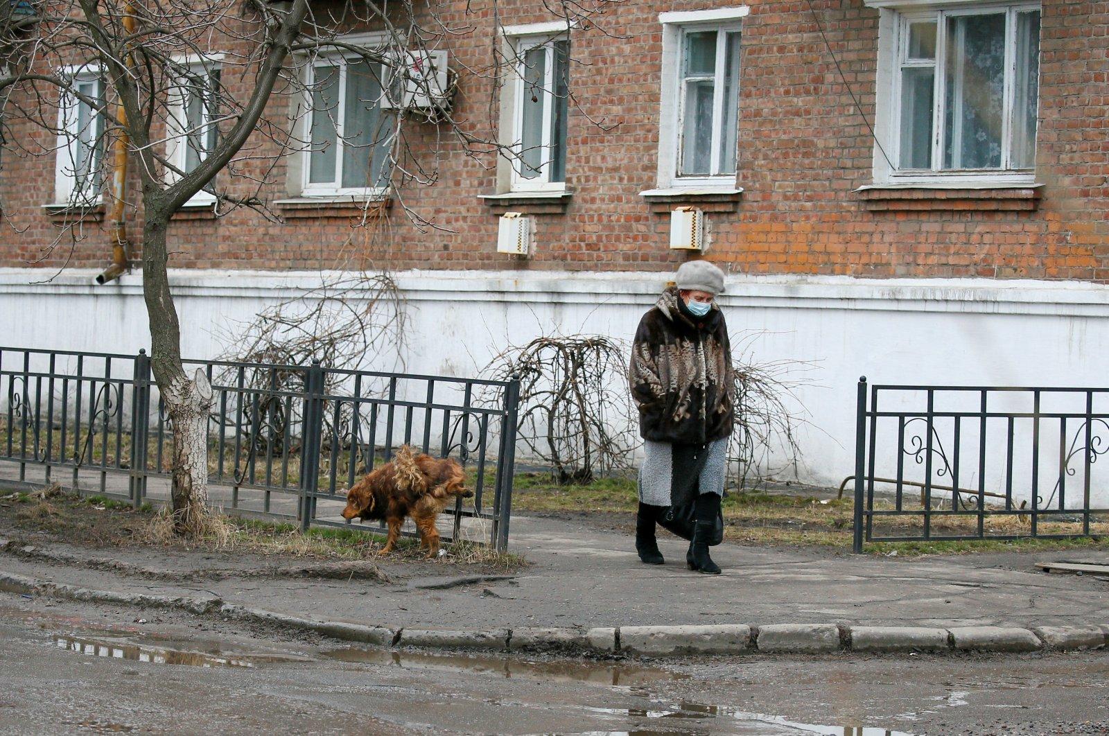 A woman walks along a street in the town of Novhorodske in Donetsk Region, Ukraine, March 3, 2021. (Reuters Photo)