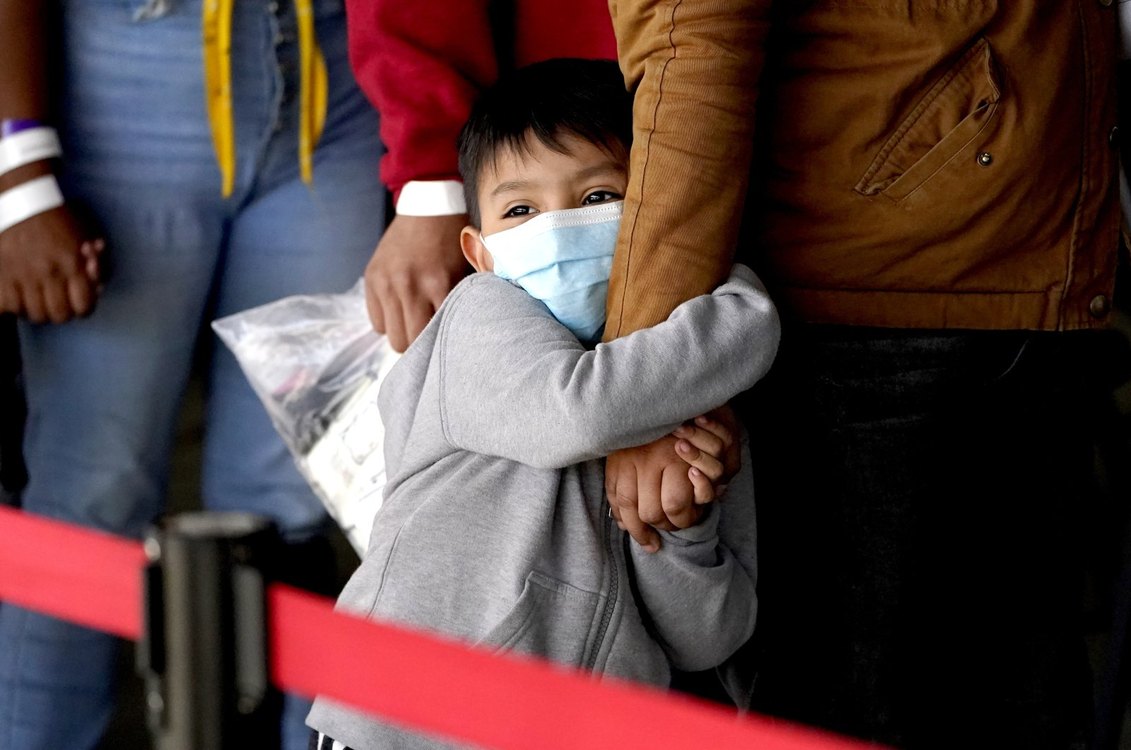 A migrant child holds onto a woman's arm as they wait to be processed by a humanitarian group after being released from U.S. Customs and Border Protection custody at a bus station, in Brownsville, Texas, U.S, Wednesday, March 17, 2021. (AP Photo)