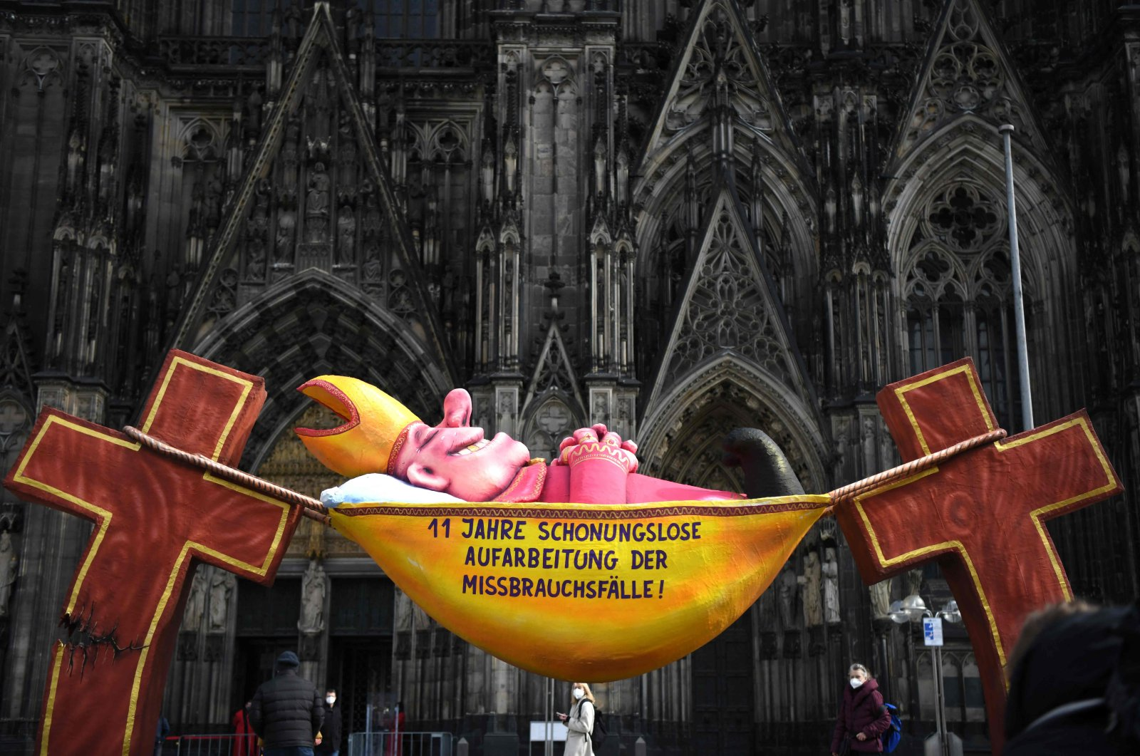 """A sculpture by artist Jacques Tilly with the slogan """"11 years of relentless investigation of the abuse cases!"""" is seen in front of the Cologne Cathedral in Cologne, western Germany, on March 18, 2021. (AFP Photo)"""