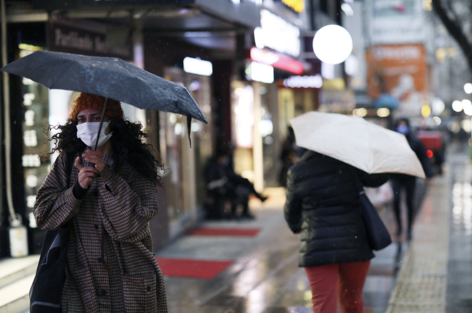 A woman with a face mask walks in the rain on a street, in Ankara, Turkey, on March 16, 2021. (AP Photo)
