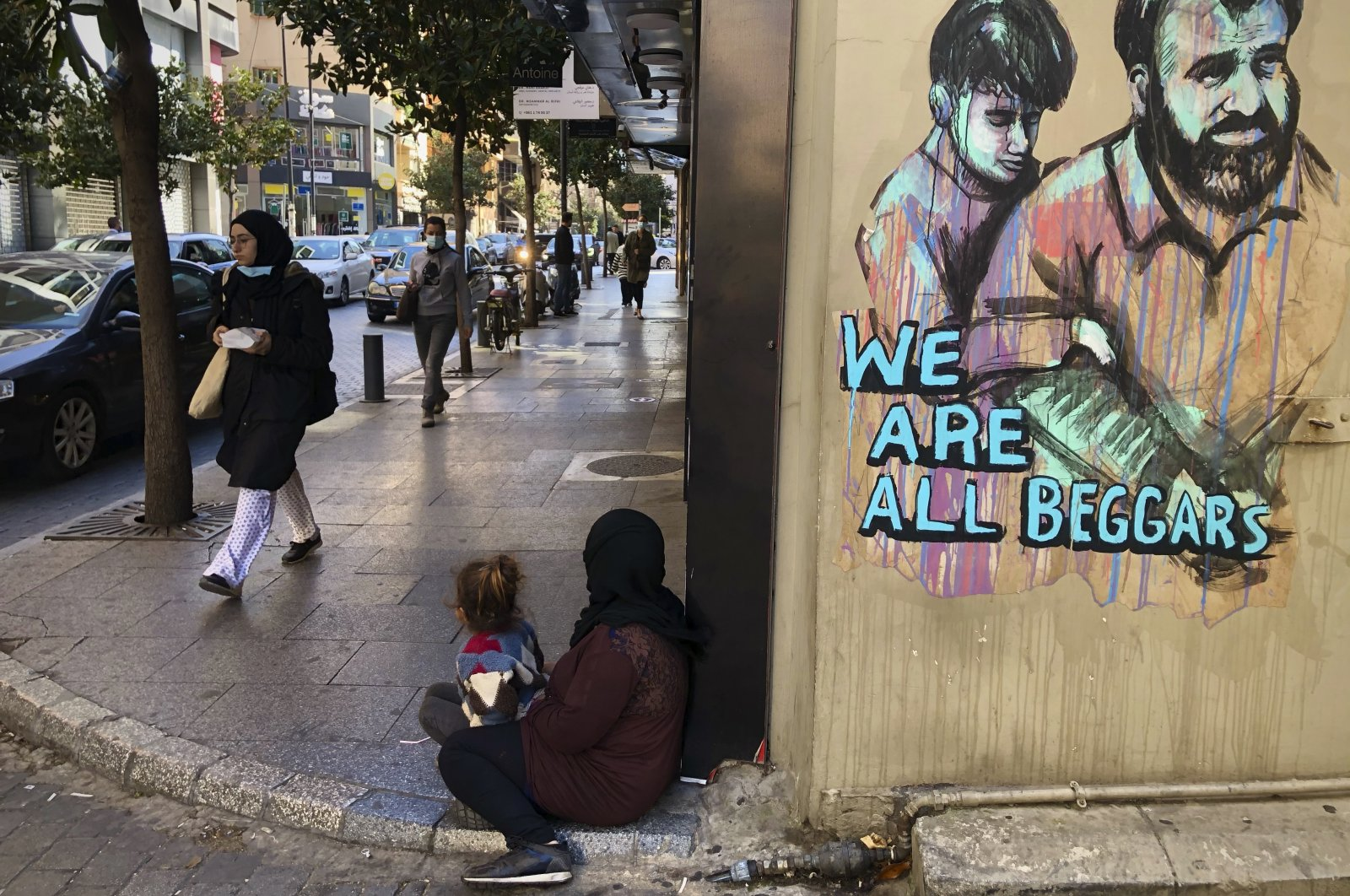Passersby walk by a woman (center) sitting on the ground with her daughter begging on Beirut's commercial Hamra Street, in Beirut, Lebanon, March 16, 2021. (AP Photo)