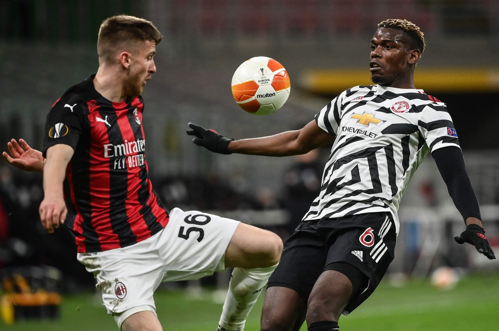 AC Milan's Belgian forward Alexis Saelemaekers (L) and Manchester United's French midfielder Paul Pogba go for the ball during a UEFA Europa League round of 16, second leg match at San Siro stadium in Milan on March 18, 2021. (AFP Photo)