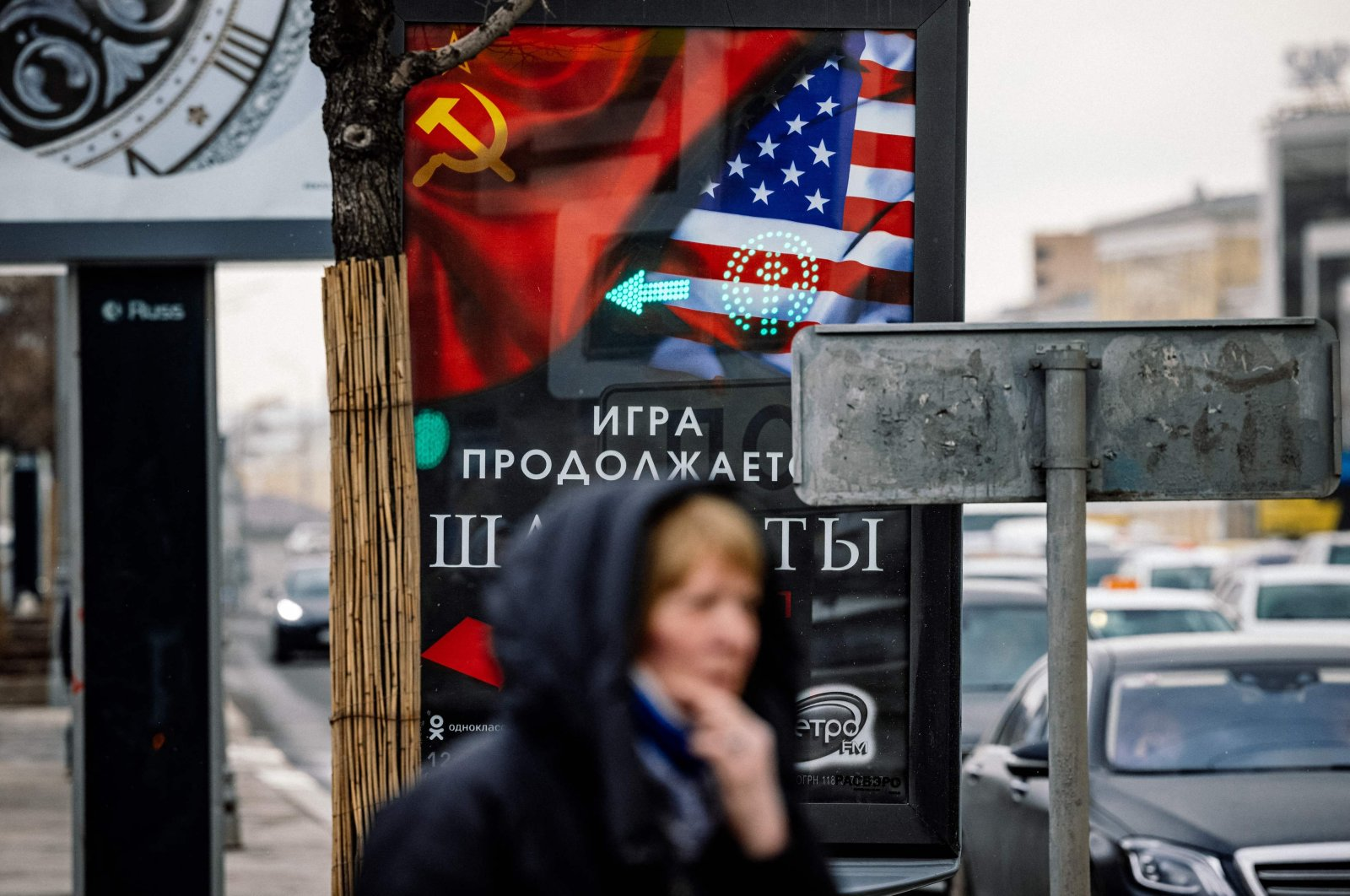 """A woman stands in front of a poster with images of a Soviet and U.S. flag announcing the legendary musical """"Chess"""" in Moscow, Russia, March 18, 2021. (AFP Photo)"""