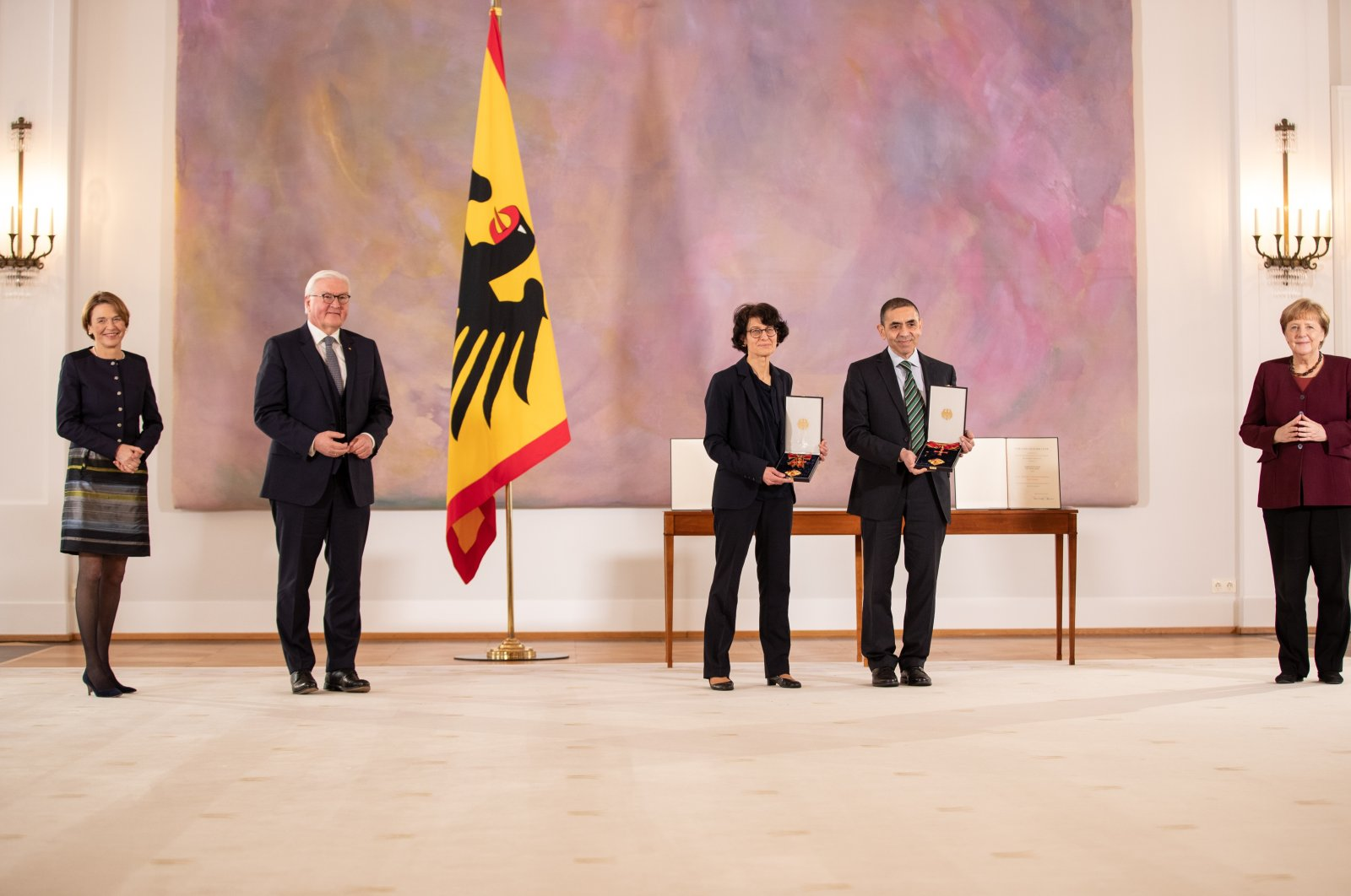 Özlem Türeci (3rd L) and her husband Uğur Şahin (2nd R) pose with their medals next to President Frank-Walter Steinmeier (2nd L) and Chancellor Angela Merkel (R), in Berlin, Germany, March 19, 2021. (AP Photo)