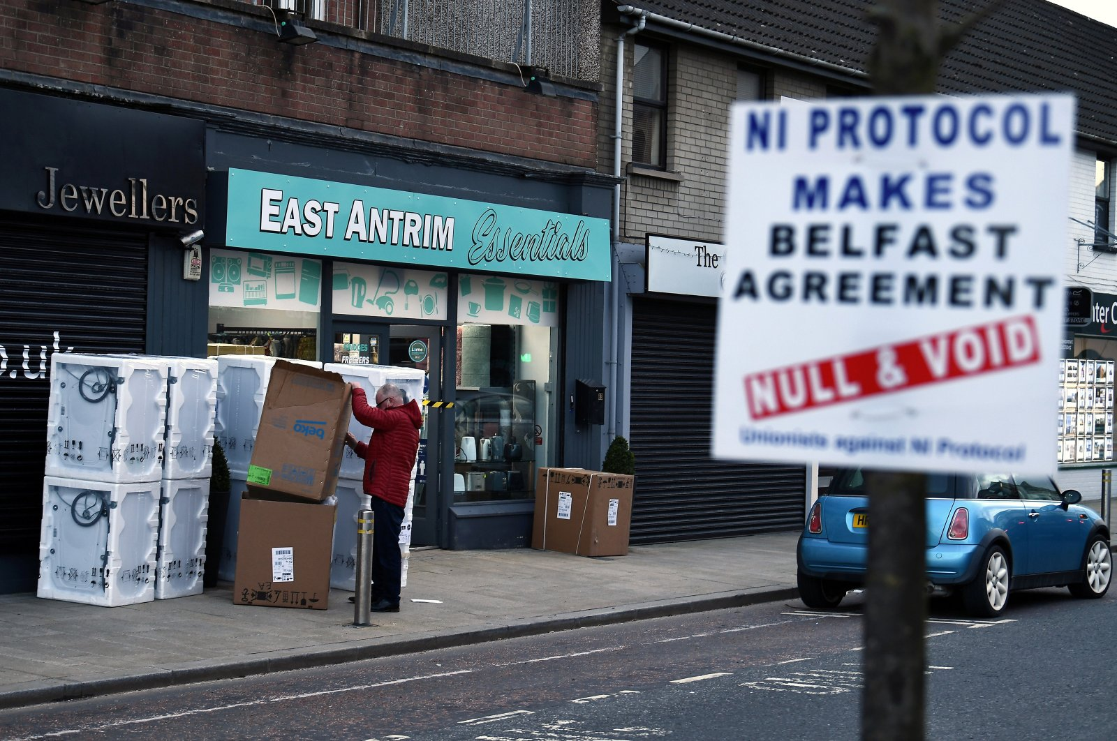 A man sorts through a delivery of washing machines, while a sign is seen across the road with a message against the Brexit border checks in relation to the Northern Ireland protocol, Larne, Northern Ireland, Feb. 12, 2021. (REUTERS)