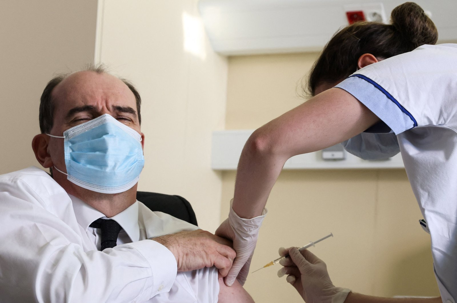 Prime Minister Jean Castex, 55-years-old, reacts as he is vaccinated with the AstraZeneca COVID-19 vaccine in a hospital, on the outskirts of Paris, France, March 19, 2021. (THOMAS COEX / POOL / AFP)
