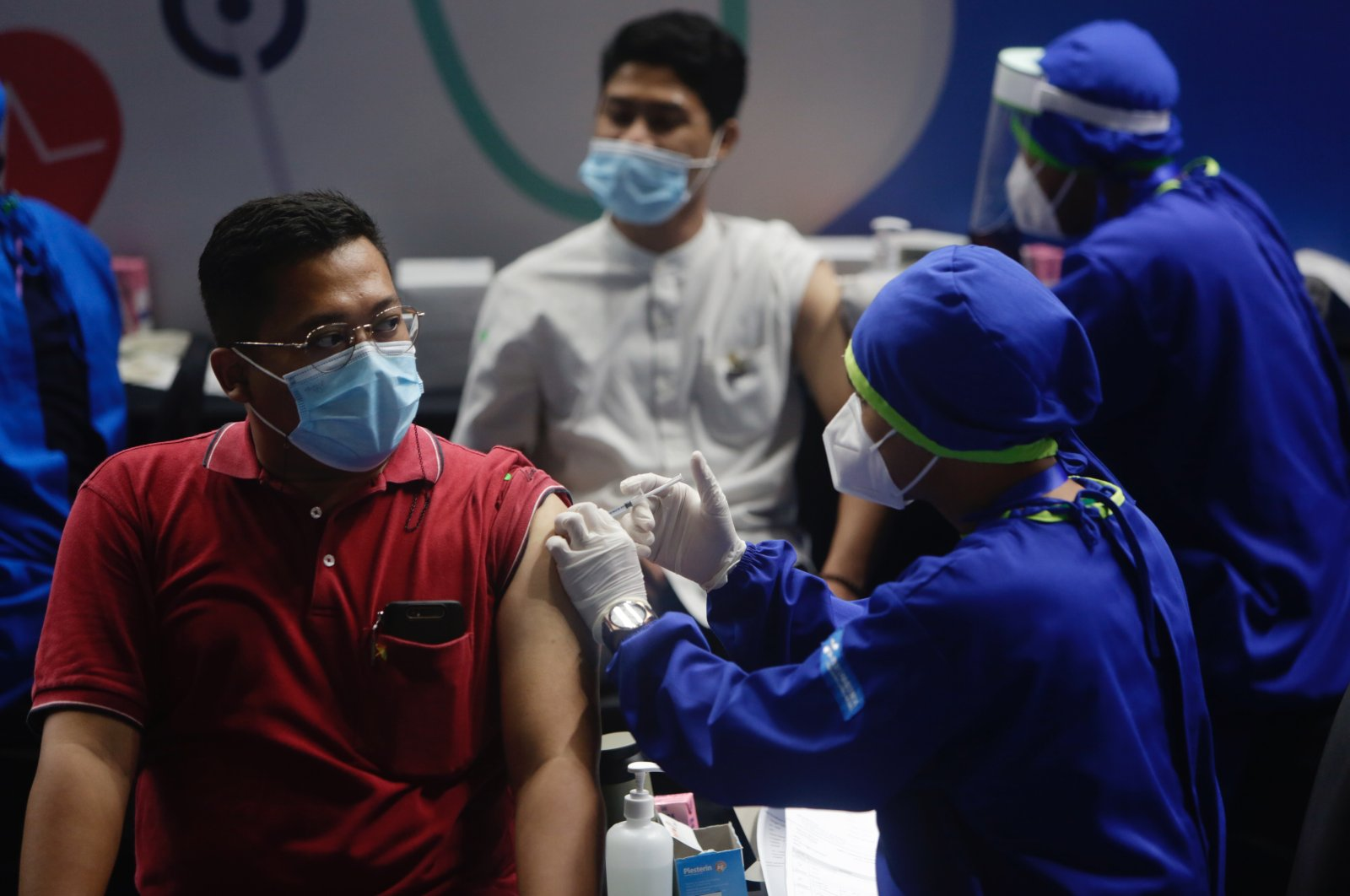 Two men receive shots of COVID-19 vaccines during a mass vaccination drive in Jakarta, Indonesia, March 15, 2021. (EPA Photo)