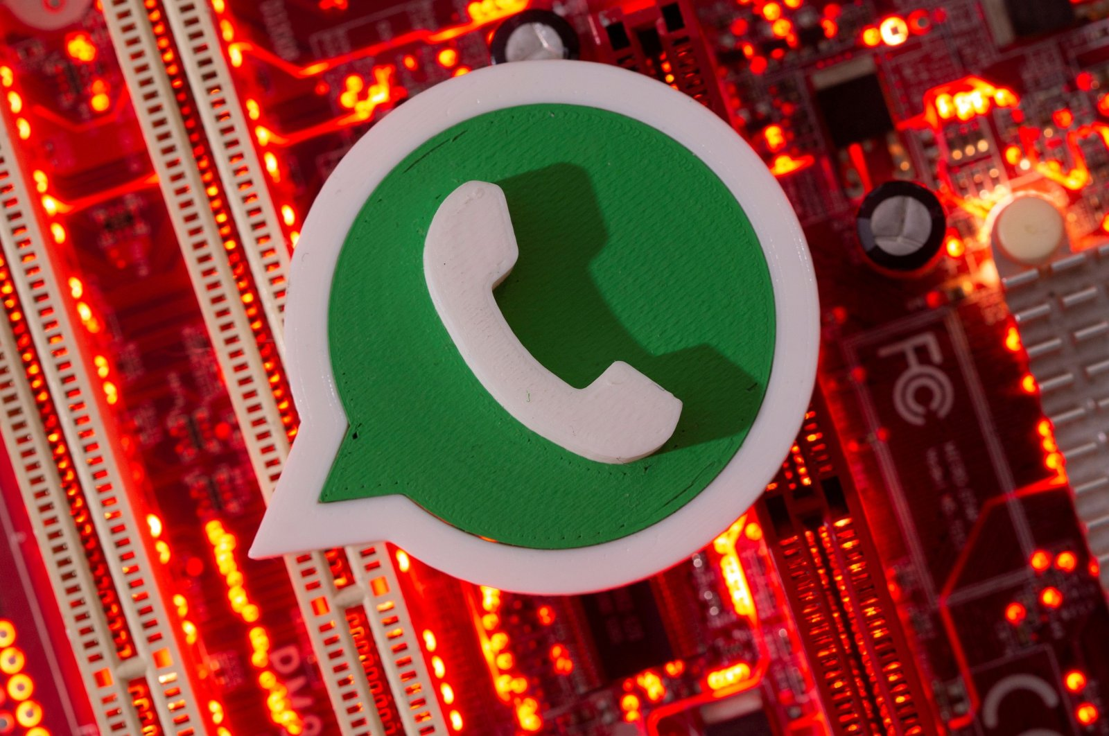 A 3D printed WhatsApp logo is placed on a computer motherboard, January 21, 2021. (Reuters Photo)