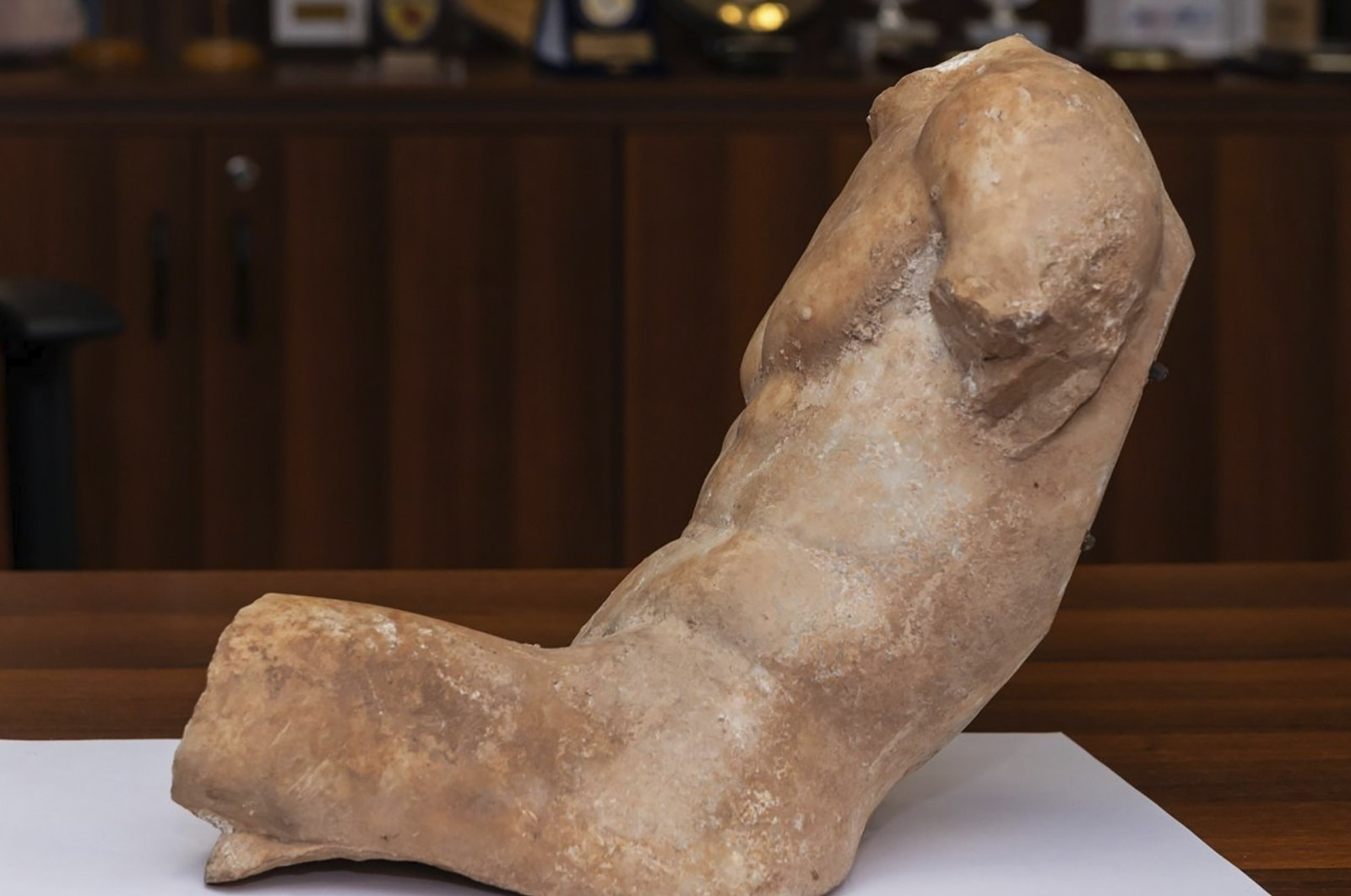 A 5th century B.C. statue about 37 centimeters (14.5 inches), depicting a seated young man who slightly reclines, can be seen, Athens, Greece, March 19, 2021. (Greek Police via AP)