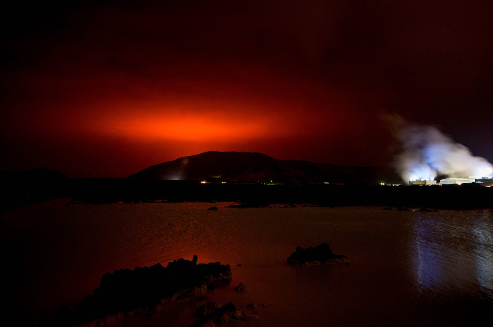 The red shimmer from magma flowing out from the erupting Fagradalsfjall volcano behind the landmark Blue Lagoon, some 45 kilometers west of capital Reykjavik, Iceland, March 19, 2021. (AFP Photo)