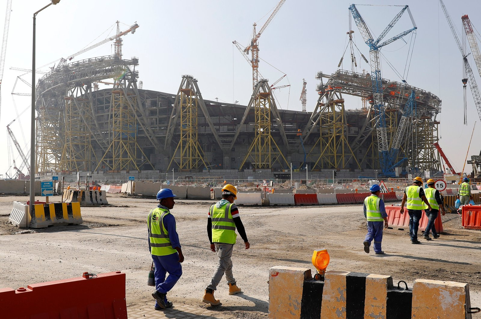 This file photo shows workers walking towards the construction site of the Lusail Stadium which will be build for the upcoming 2022 FIFA World Cup during a stadium tour in Doha, Qatar, Dec.20, 2019. (Reuters Photo)