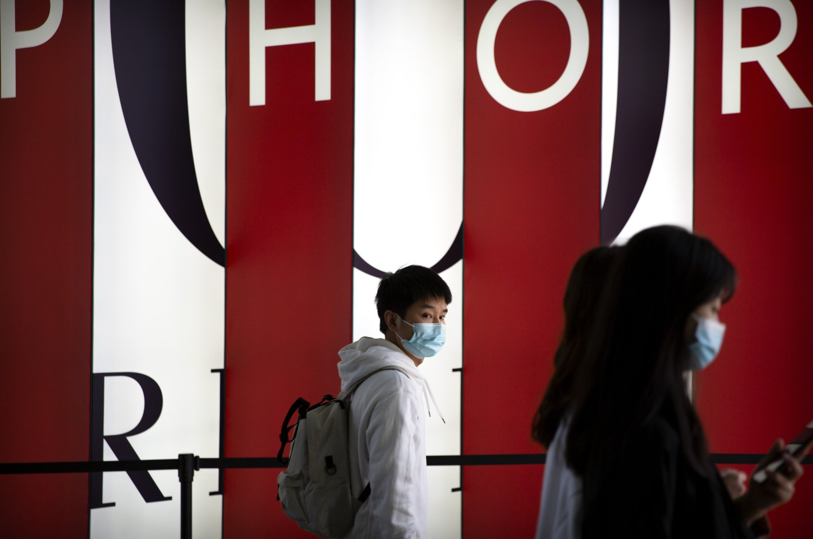 People wearing face masks walk at a shopping center in Beijing, China, March 20, 2021. (AP Photo)