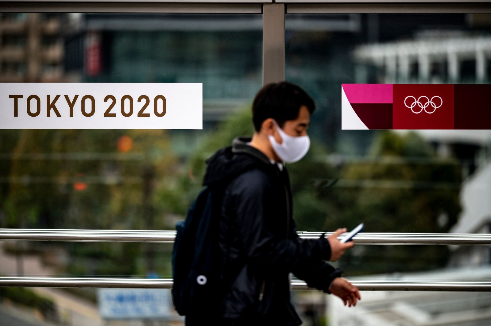 A man walks past logos of the Tokyo 2020 Olympic Games banners in Tokyo, Japan, March 20, 2021. (AFP Photo)
