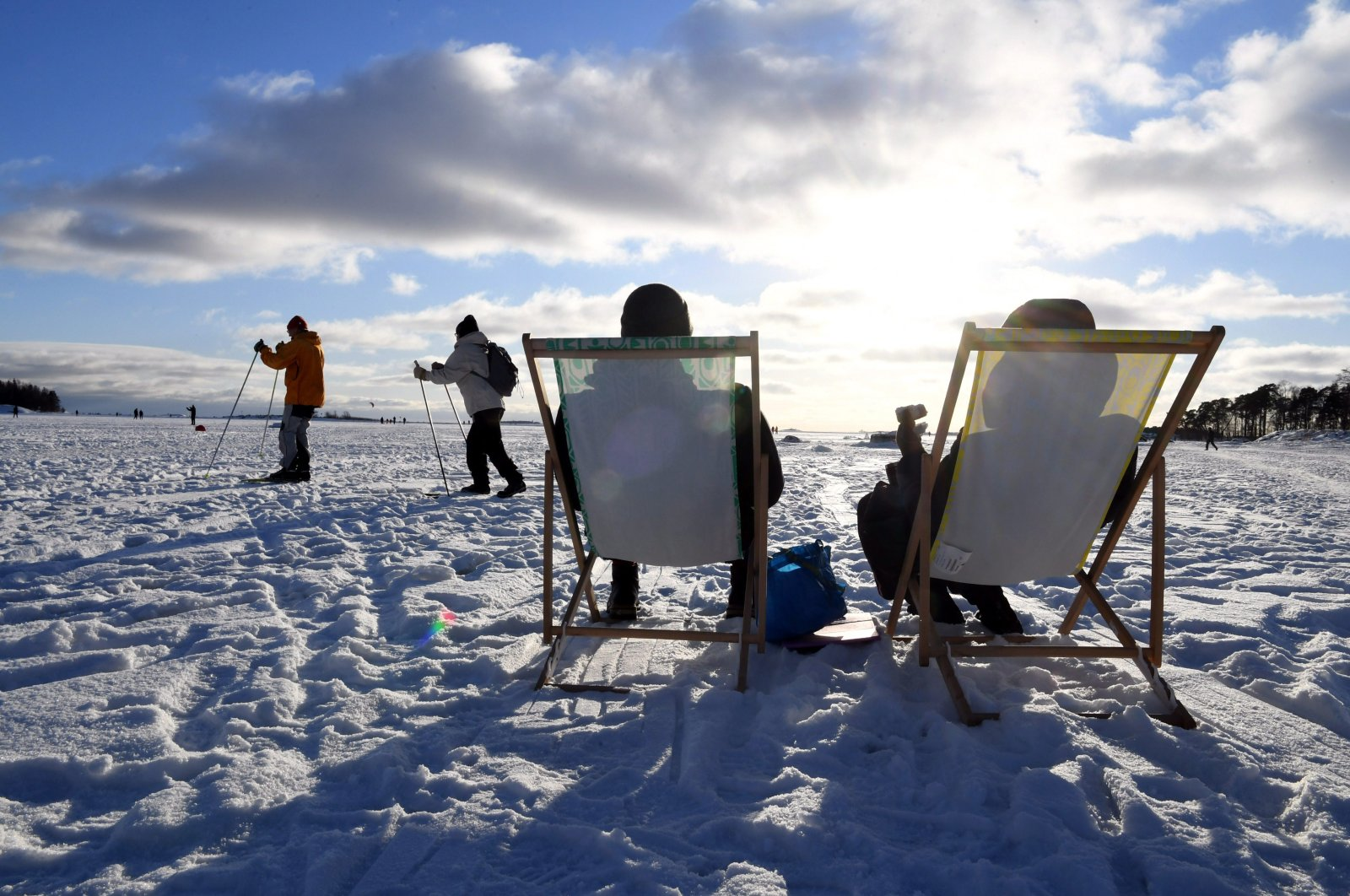 People sit in the sunshine as others ski by, during a sunny winter day on waterfront ice of Helsinki, Finland on Valentine's Day February 14, 2021. (AP)