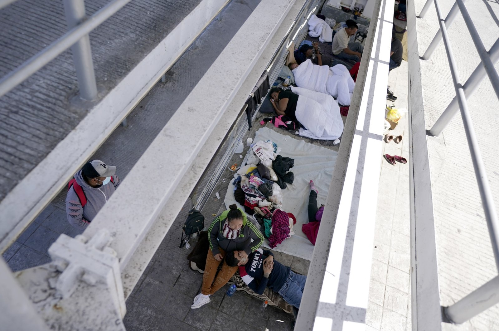 Migrants who were caught trying to sneak into the United States and deported rest under a ramp that leads to the McAllen-Hidalgo International Bridge point of entry into the U.S. in Reynosa, Mexico, on Thursday, March 18, 2021, (AP Photo)