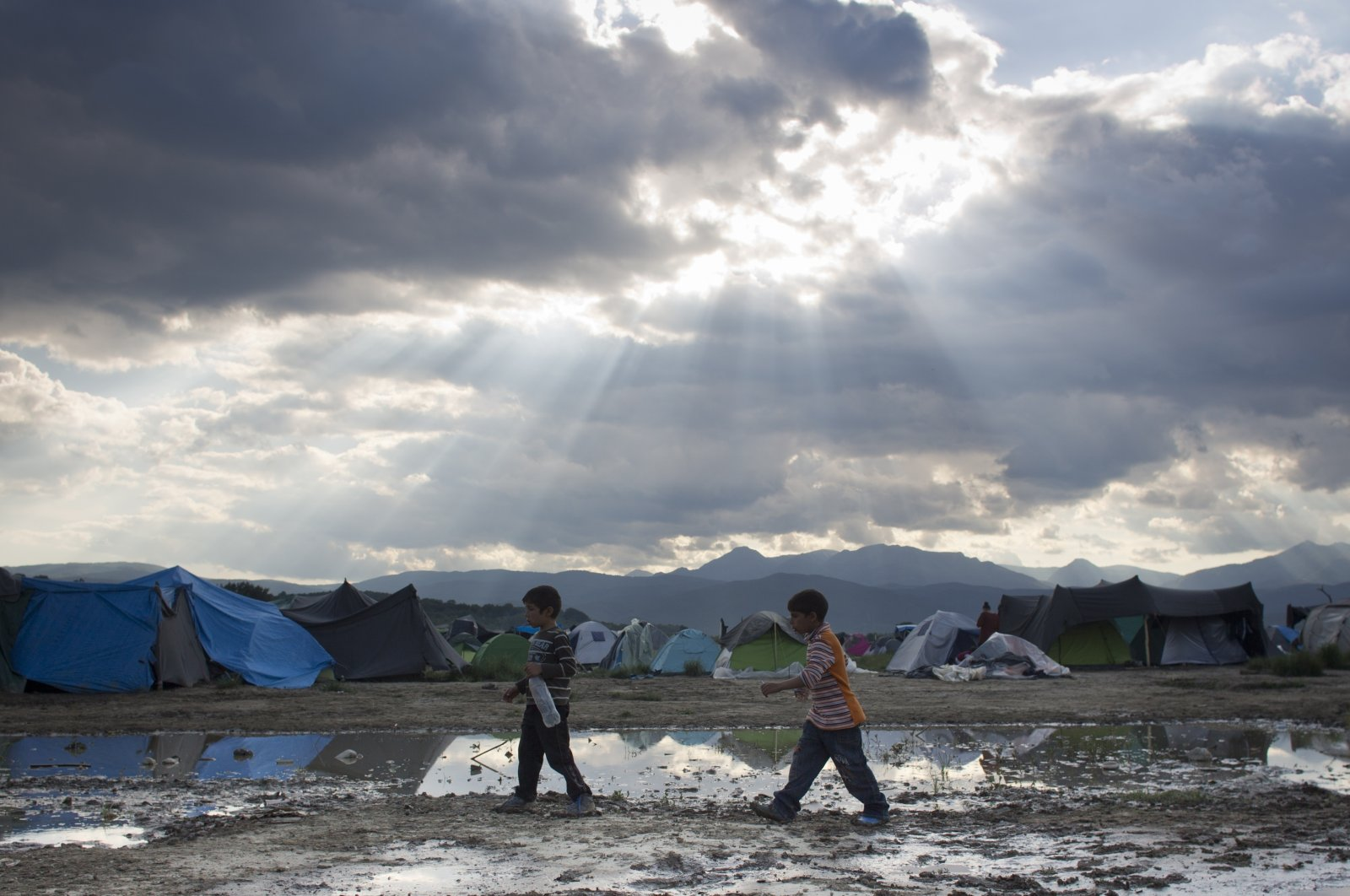 Two boys walk past groundwater at the migrant camp in Idomeni, northern Greece on May 22, 2016. (AP File Photo)
