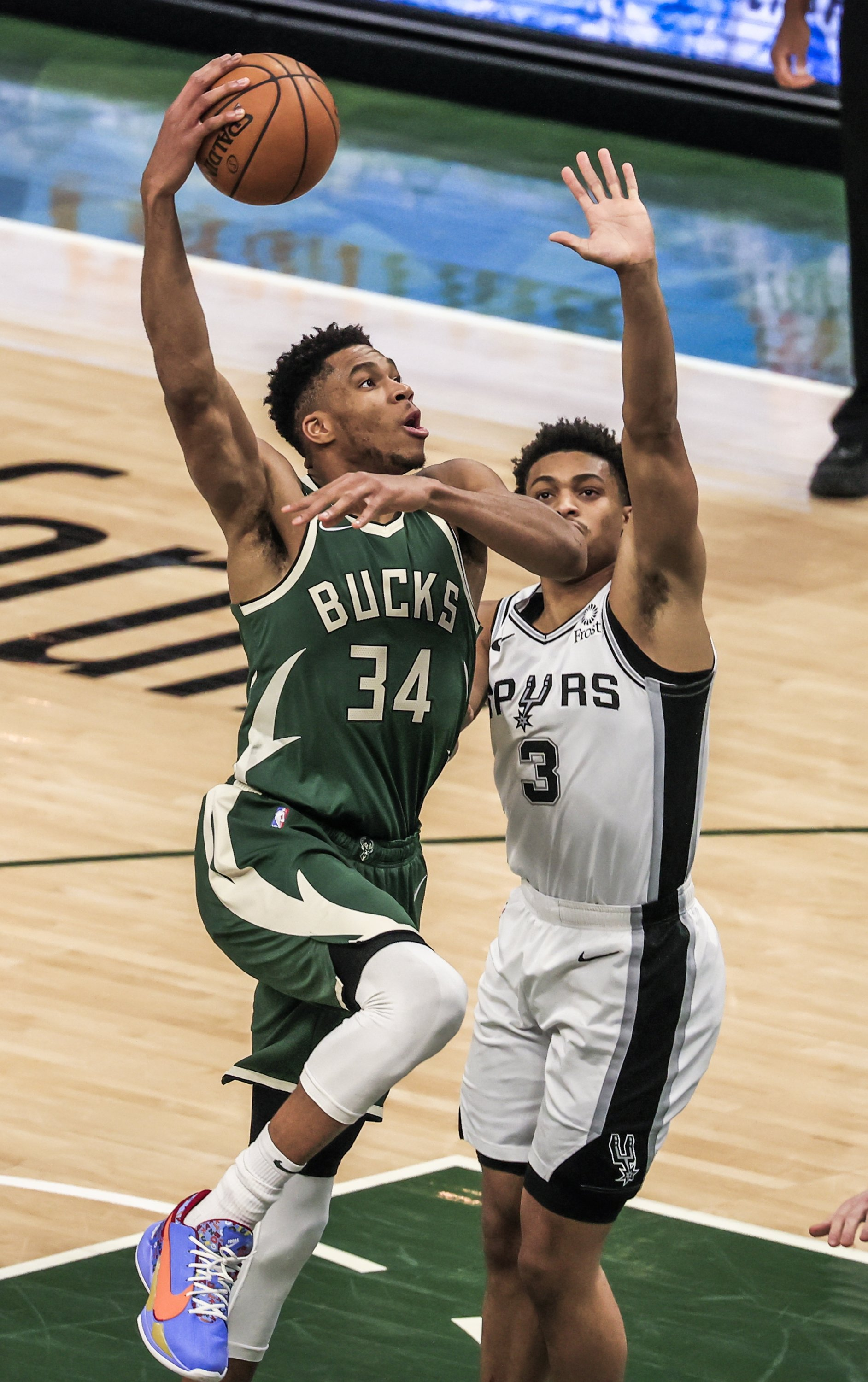 Milwaukee Bucks forward Giannis Antetokounmpo (L) shoots on San Antonio Spurs forward Keldon Johnson (R) during an NBA game at Fiserv Forum in Milwaukee, Wisconsin, March 20, 2021.  (EPA Photo)