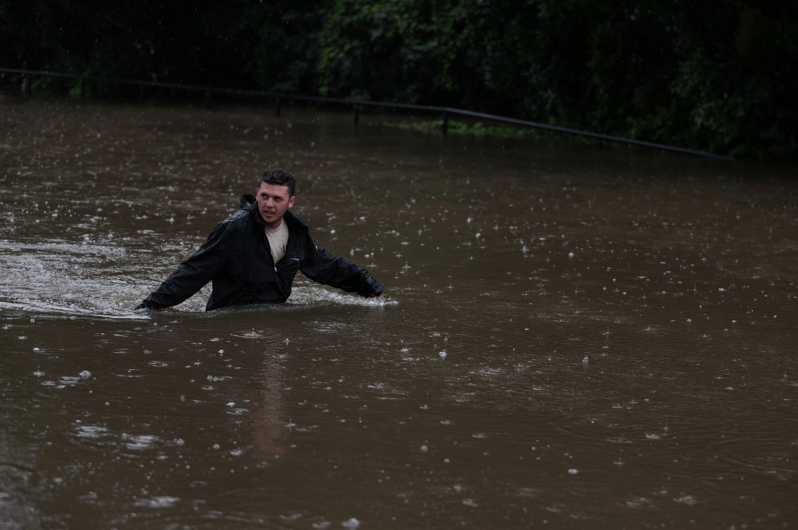 A man wades through floodwaters on a residential street near the swollen Nepean River as the state of New South Wales experiences widespread flooding and severe weather, in Sydney, Australia, March 21, 2021. (Reuters Photo)