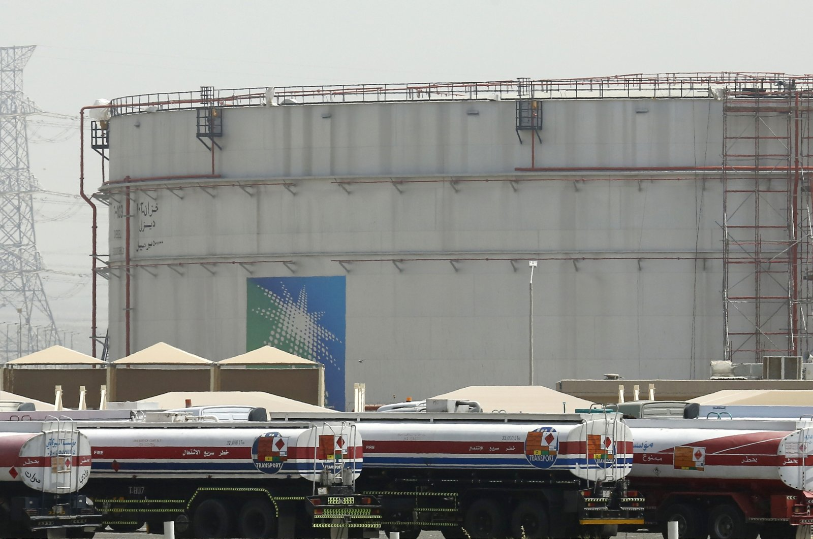 Fuel trucks line up in front of storage tanks at the North Jiddah bulk plant, an Aramco oil facility, in Jeddah, Saudi Arabia, March 21, 2021. (AP Photo)