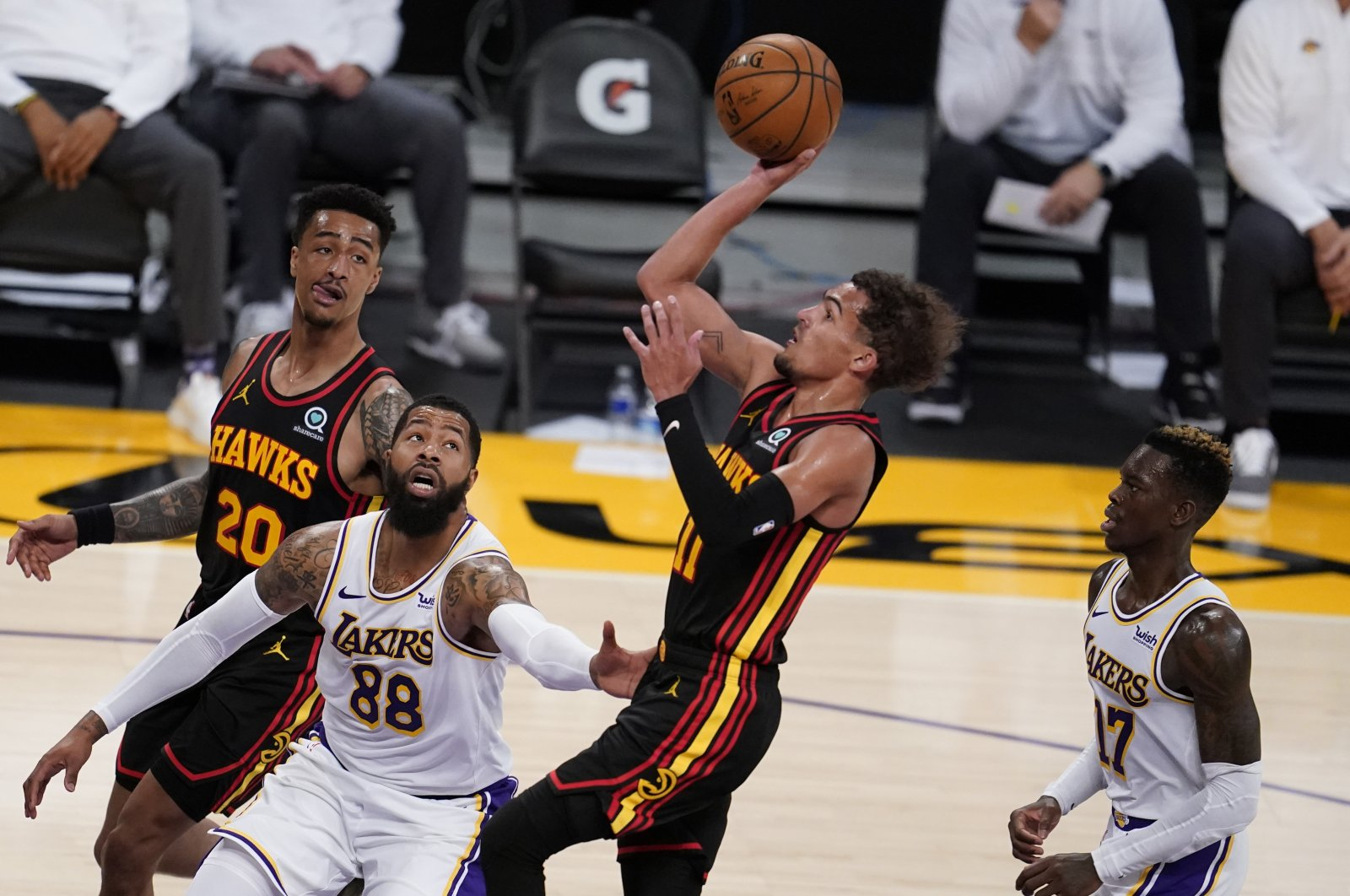 Atlanta Hawks guard Trae Young (C) shoots over Los Angeles Lakers forward Markieff Morris (L) and Dennis Schroder (R) during an NBA game, Los Angeles, U.S., March 20, 2021. (AP Photo)