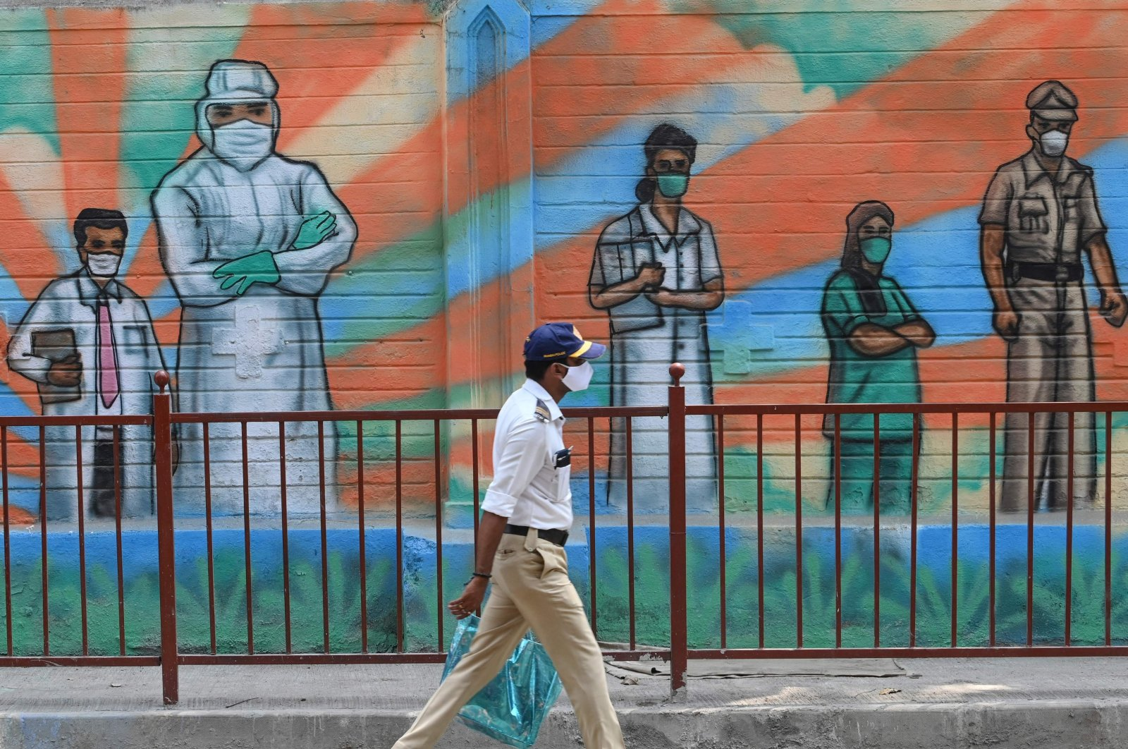 A police officer walks past a mural depicting frontline COVID-19 warriors, in Mumbai, India, on March 21, 2021. (AFP Photo)
