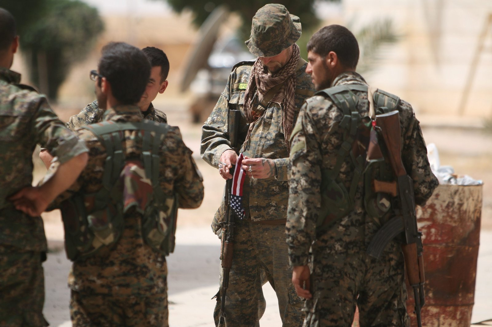 A U.S. fighter, who is fighting alongside YPG terrorists, carries his national flag as he stands with YPG members in the northern province of Raqqa, Syria, May 27, 2016. (REUTERS Photo)