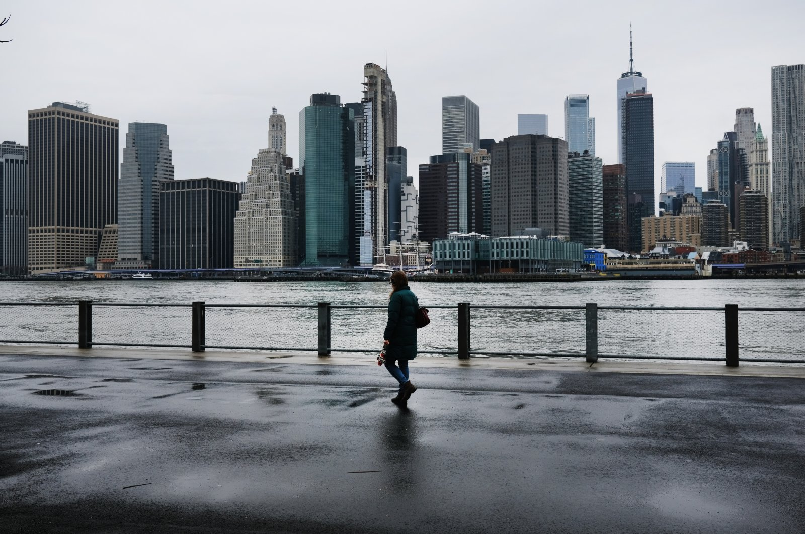 People walk in Brooklyn with lower Manhattan looming in the background amid the coronavirus pandemic, New York City, New York, U.S., March 28, 2020. (Photo by Getty Images)