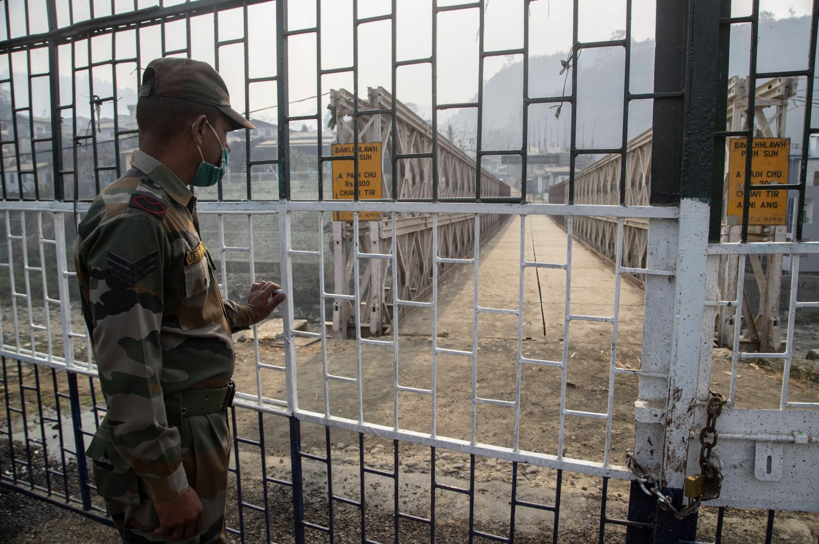 An Indian paramilitary soldier stands guard near the bridge on the Tiau river along the India-Myanmar border in Mizoram, India, March 20, 2021. (AP Photo)