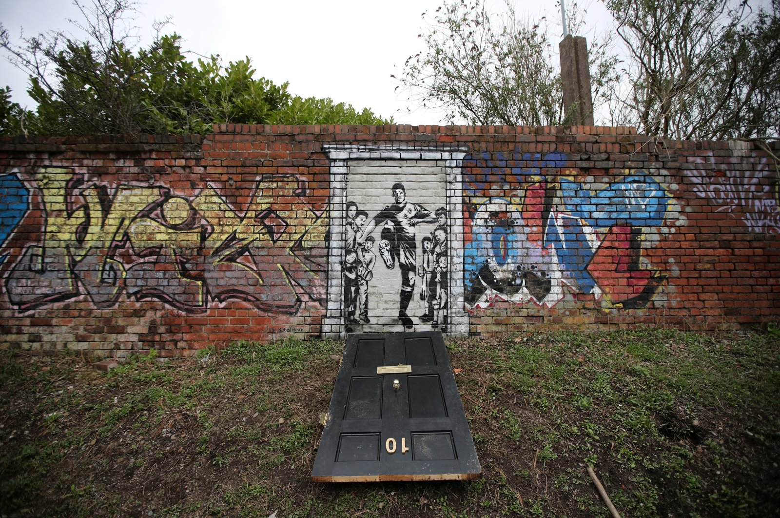 A mural of England footballer Marcus Rashford kicking down the door of No. 10 Downing St. appears on Manchester Canal in Manchester, Britain, March 21, 2021. (Reuters Photo)