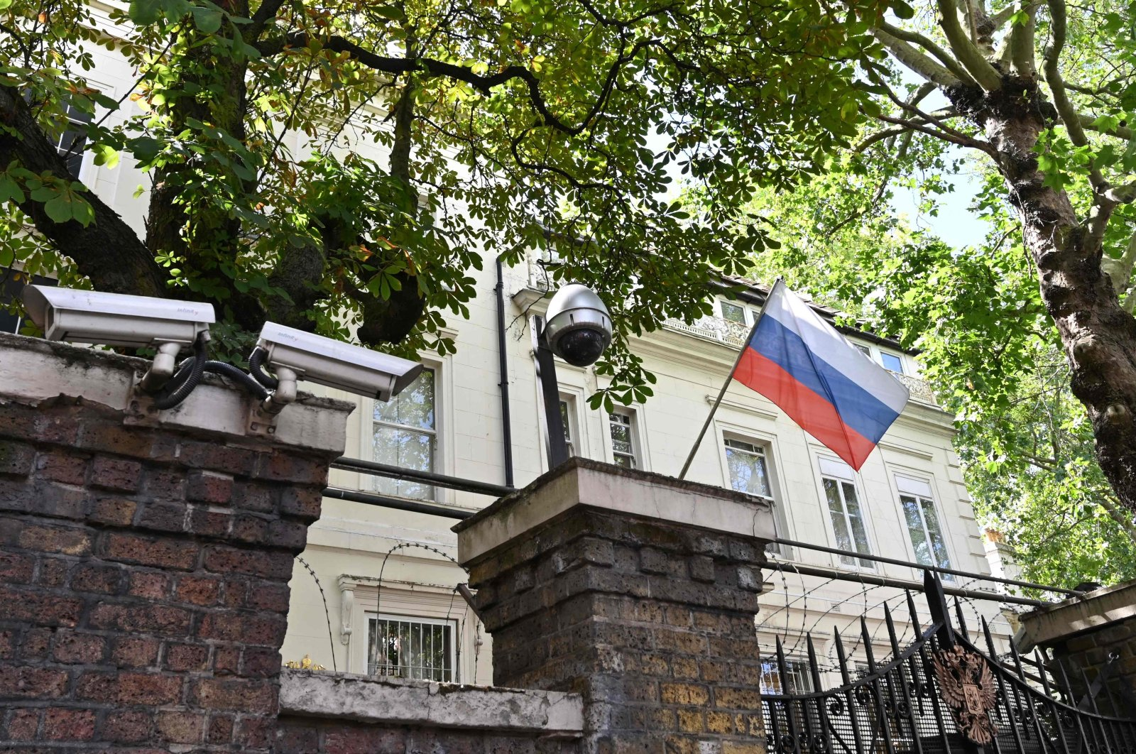A Russian flag flies by surveillance cameras at the entrance to the Russian consulate in London, July 21, 2020. (AFP Photo)