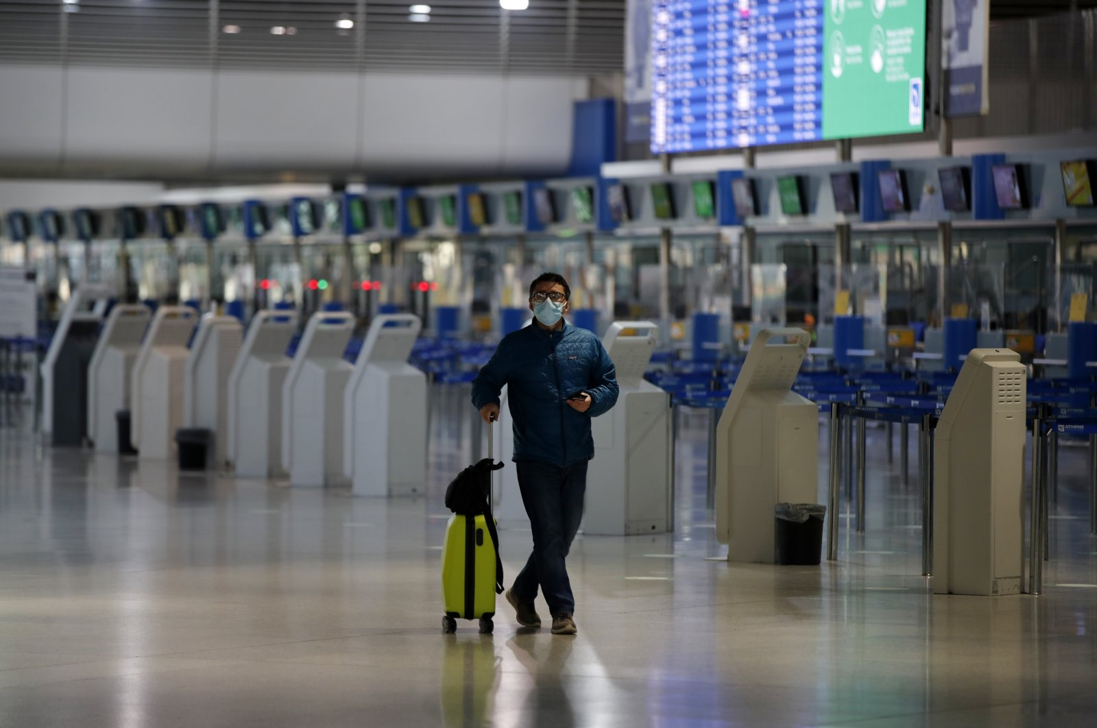 A passenger wearing a face mask to prevent the spread of the new coronavirus walks at the empty Eleftherios Venizelos International Airport during a 24-hour strike in the public sector in Athens, Greece, Oct. 15. 2020. (AP File Photo)